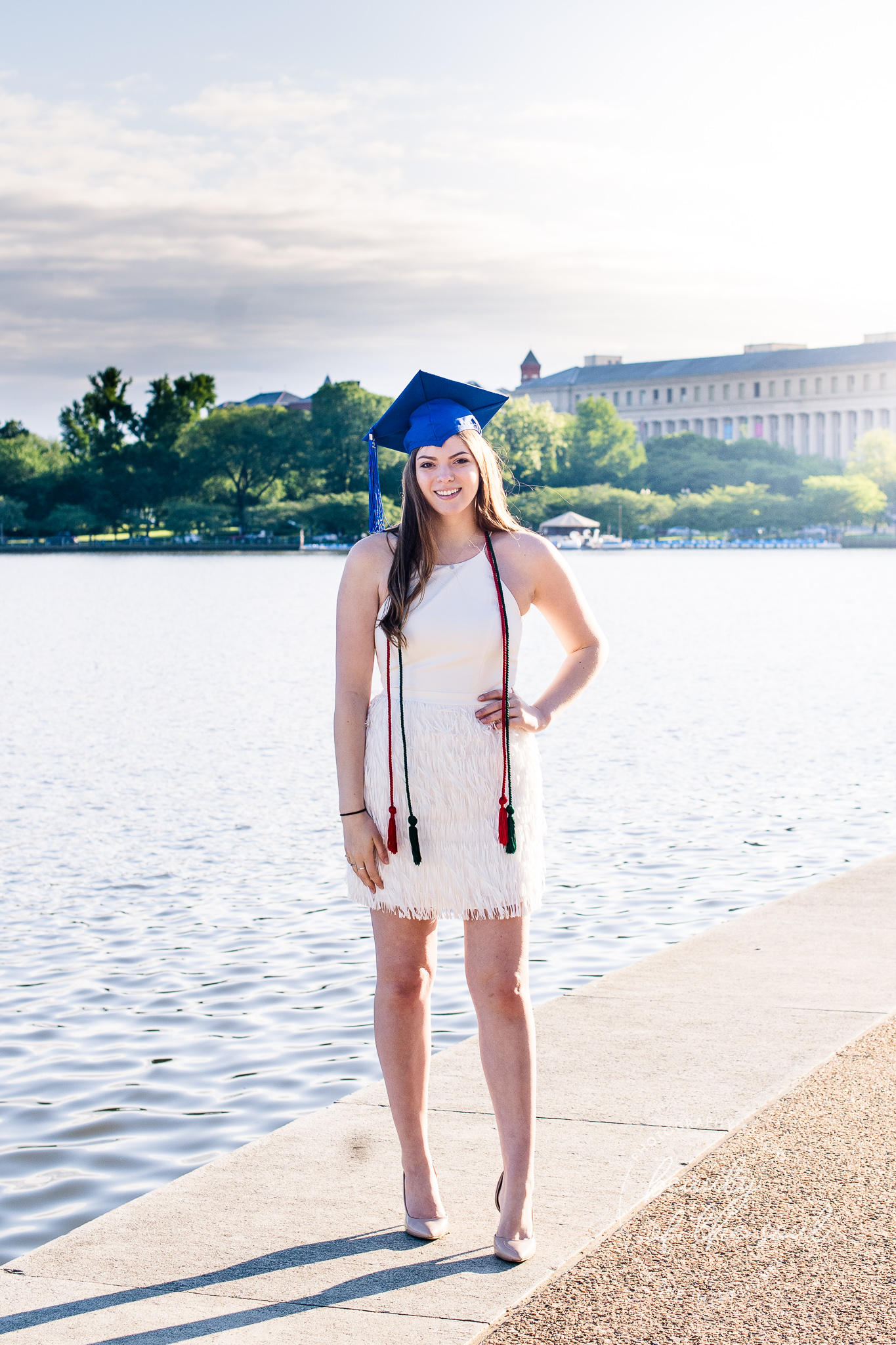 A graduate from Marymount University in Arlington, Northern Virginia standing beside the Potomac River by the Tidal Basin for her cap and gown session in Washington, DC