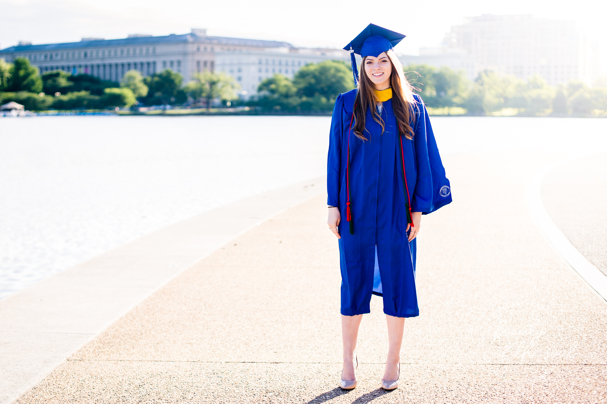A graduate from Marymount University in Arlington, Northern Virginia standing beside the Potomac River at the Tidal Basin for her cap and gown session in Washington, DC