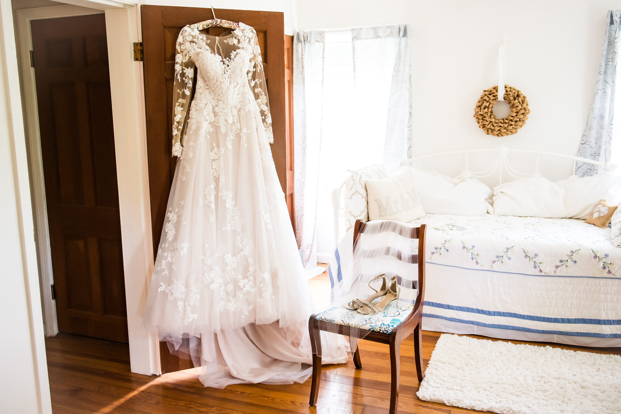 A modest lace wedding dress hanging on the door of the bridal suite at the Barns at Hamilton Station Vineyard in Leesburg, Northern Virginia before a traditional Catholic wedding