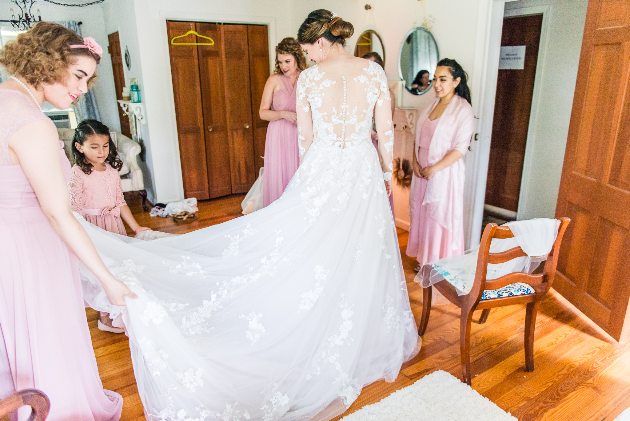 Bridesmaids in pink dresses help the bride get ready in her modest lace wedding dress with sleeves in the bridal suite at The Barns at Hamilton Station Vineyard in Leesburg, Northern Virginia before her traditional Catholic wedding