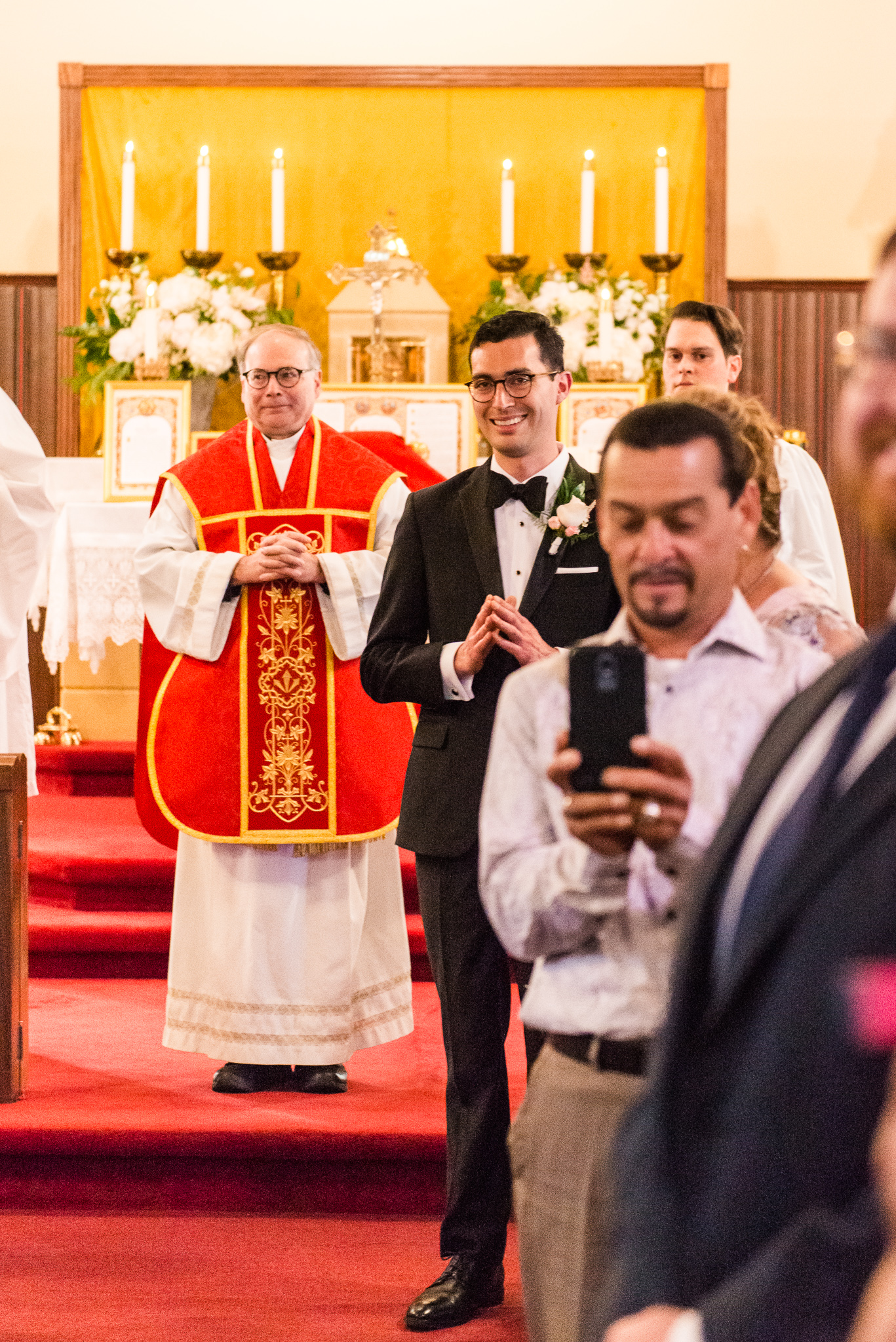 A groom looking up the aisle at his bride for the first time on their wedding day during a Catholic wedding ceremony at the Chapel of Immaculate Conception in Leesburg, Northern Virginia