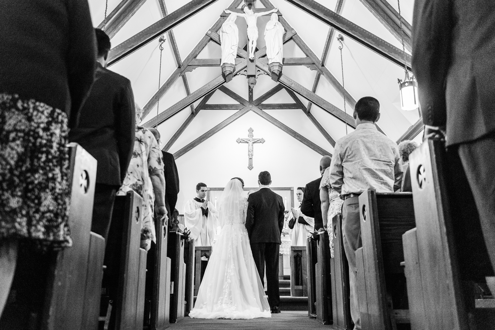A bride and groom stand before the altar and crucifix at the front of the church during a Catholic wedding ceremony at the Chapel of Immaculate Conception in Leesburg, Northern Virginia
