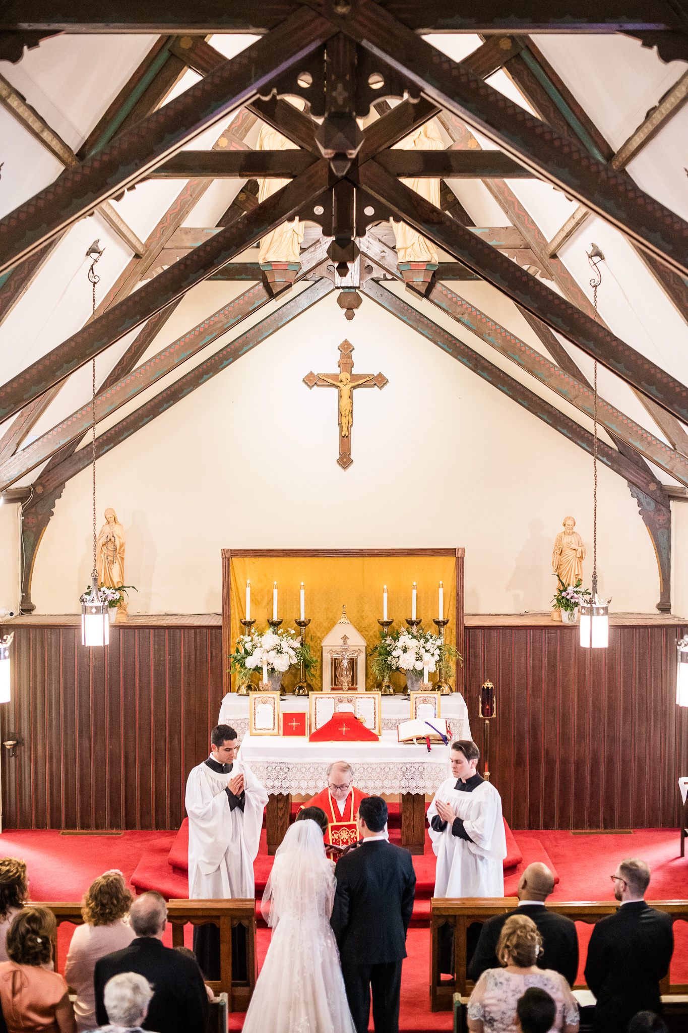 A bride and groom stand before the altar during a Catholic wedding ceremony at the Chapel of Immaculate Conception in Leesburg, Northern Virginia