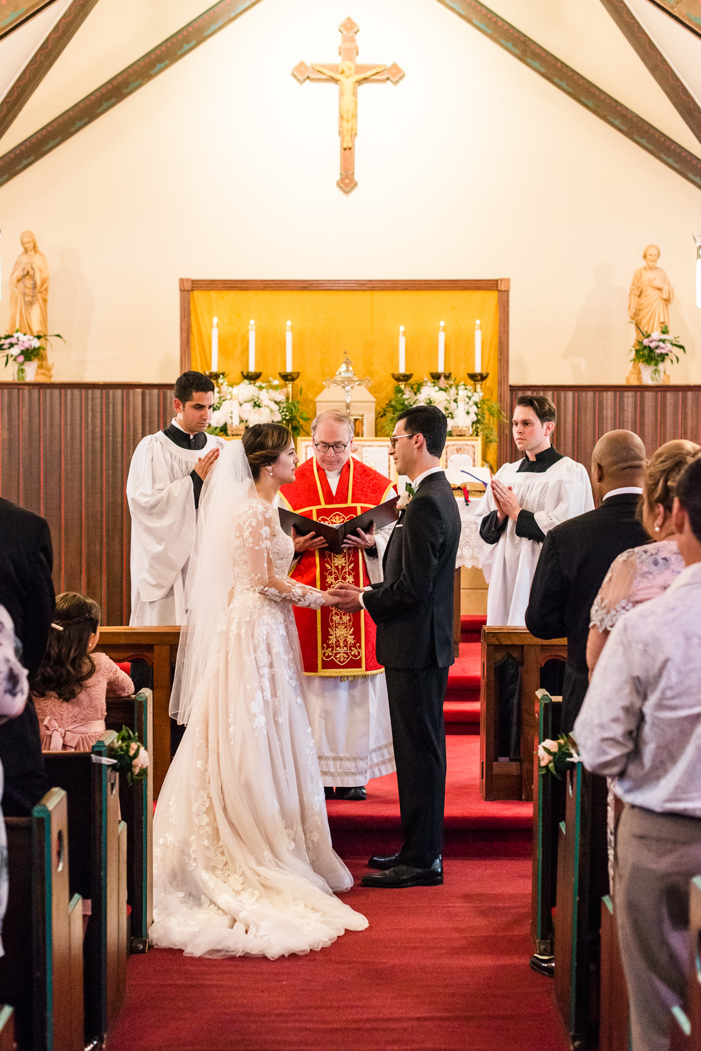 A bride and groom profess their vows at the altar during a Catholic wedding ceremony at the Chapel of Immaculate Conception in Leesburg, Northern Virginia