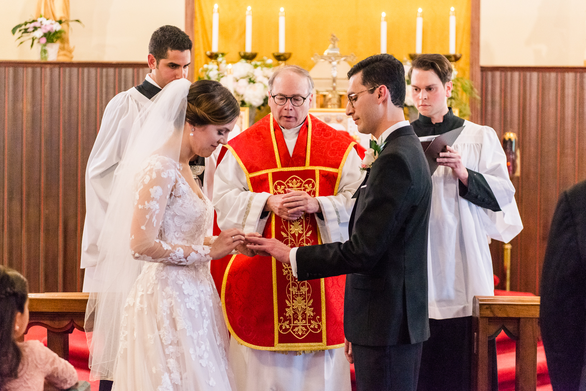A bride and groom exchange rings as she puts his ring on his finger during a Catholic wedding ceremony at the Chapel of Immaculate Conception in Leesburg, Northern Virginia