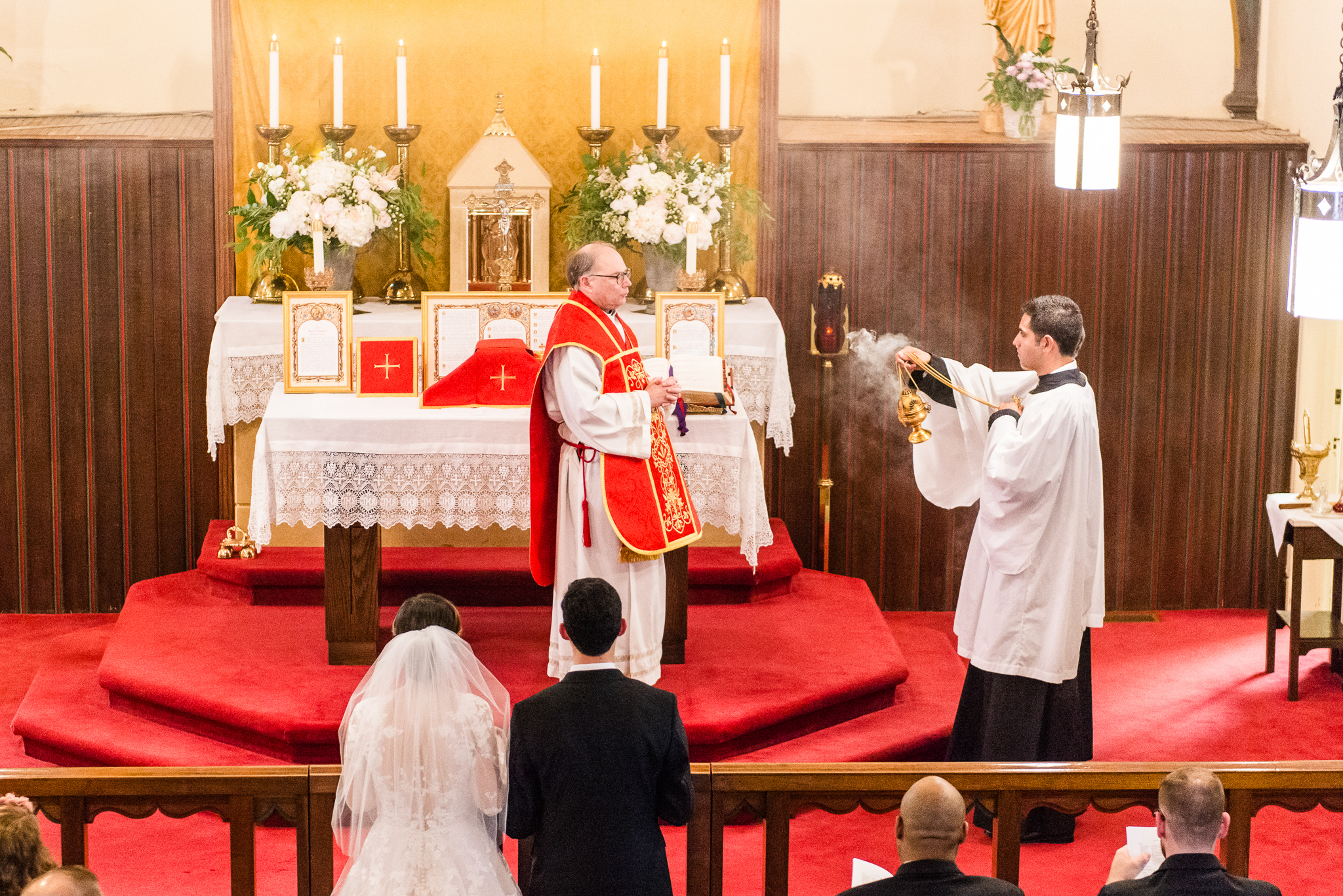 An altar server spreads incense before a priest for a Traditional Latin Mass during a Catholic wedding ceremony at the Chapel of Immaculate Conception in Leesburg, Northern Virginia
