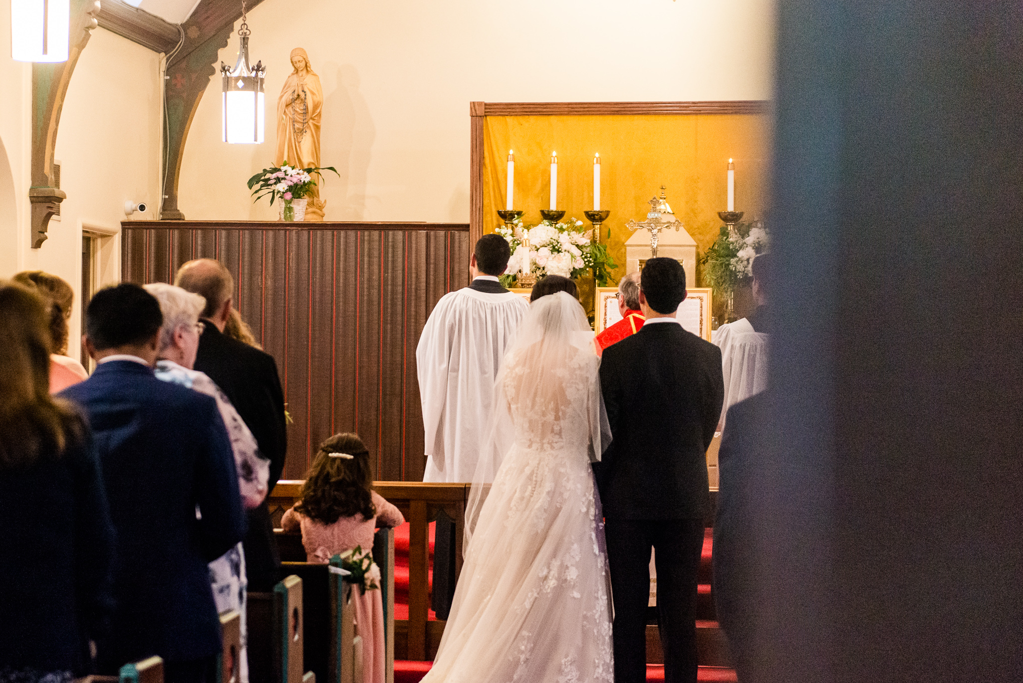 A bride and groom stand and reflect upon the Ave Maria being sung before a statue of Mary during a Catholic wedding ceremony at the Chapel of Immaculate Conception in Leesburg, Northern Virginia