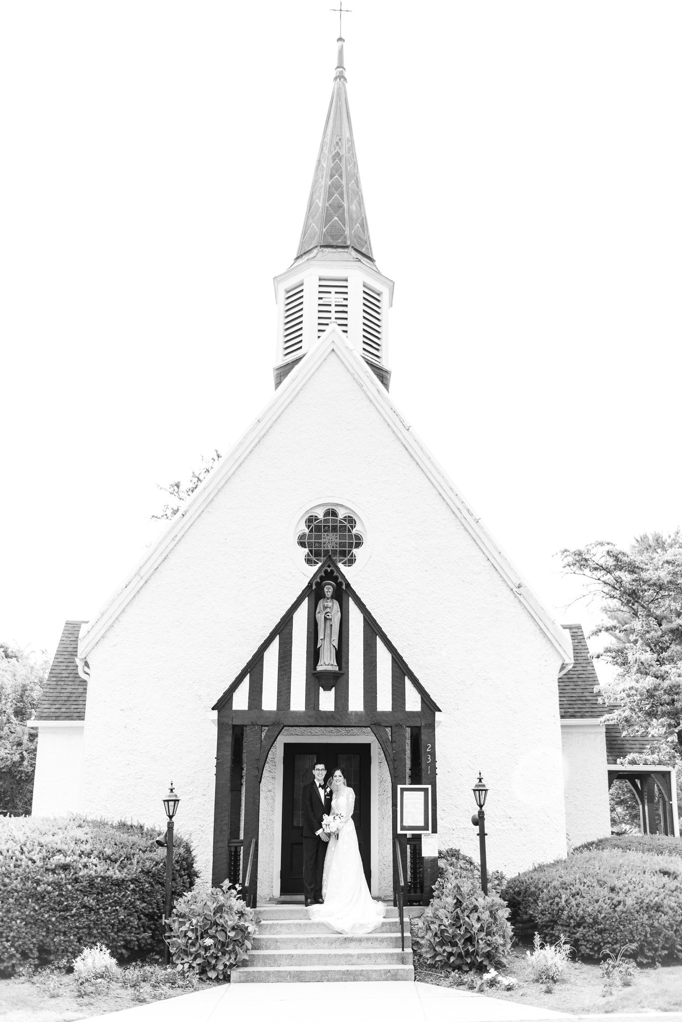 A traditional Catholic bride and groom pose for a classic portrait outside the Chapel of Immaculate Conception in Leesburg, Northern Virginia