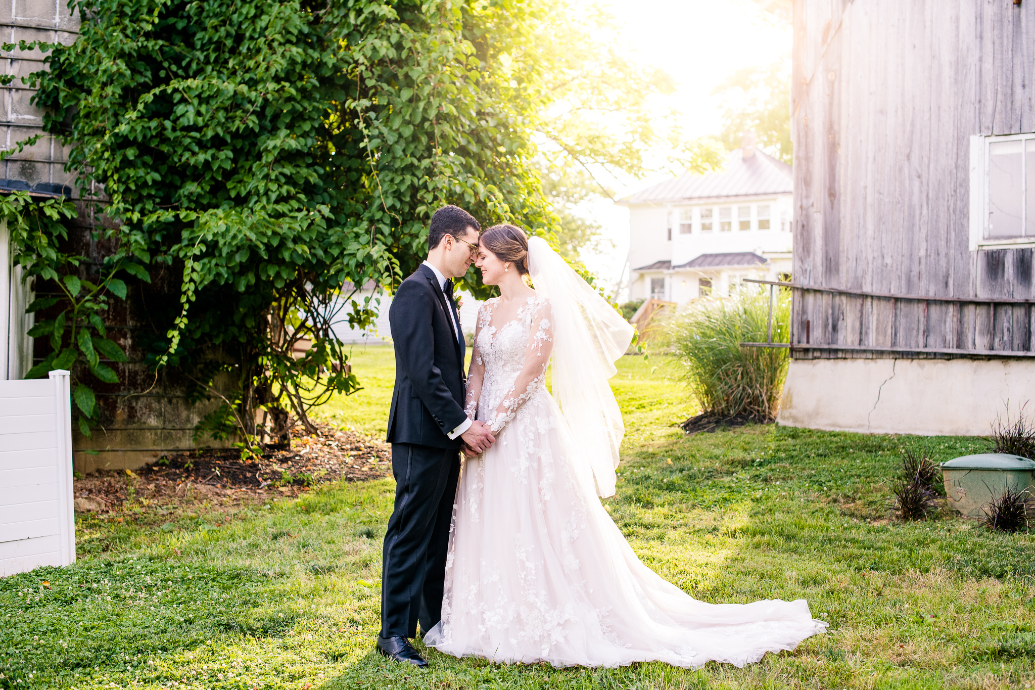 A bride and groom hold hands and lean their foreheads together during golden hour at The Barns at Hamilton Station Vineyard in Leesburg, Northern Virginia