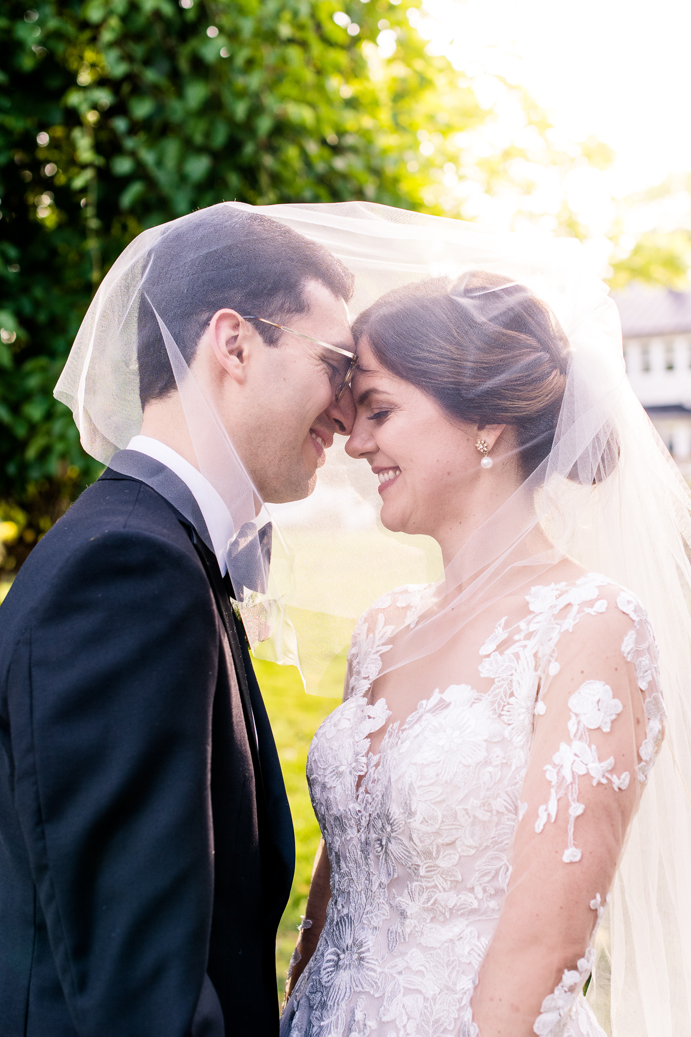 A bride and groom lean in to touch noses for an intimate moment under her veil during golden hour at The Barns at Hamilton Station Vineyard in Leesburg, Northern Virginia