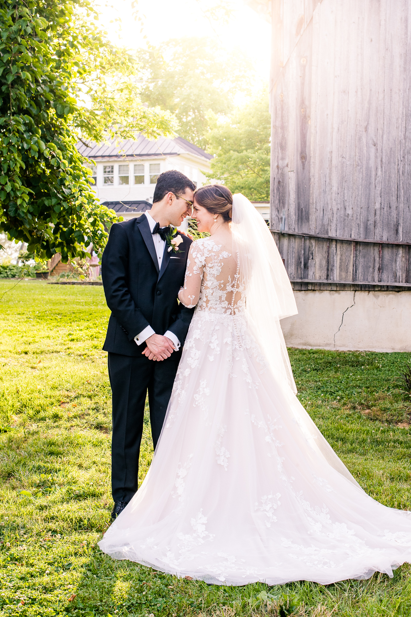 A bride and groom lean their foreheads together as the bride shows off the lace back of her dress during golden hour at The Barns at Hamilton Station Vineyard in Leesburg, Northern Virginia