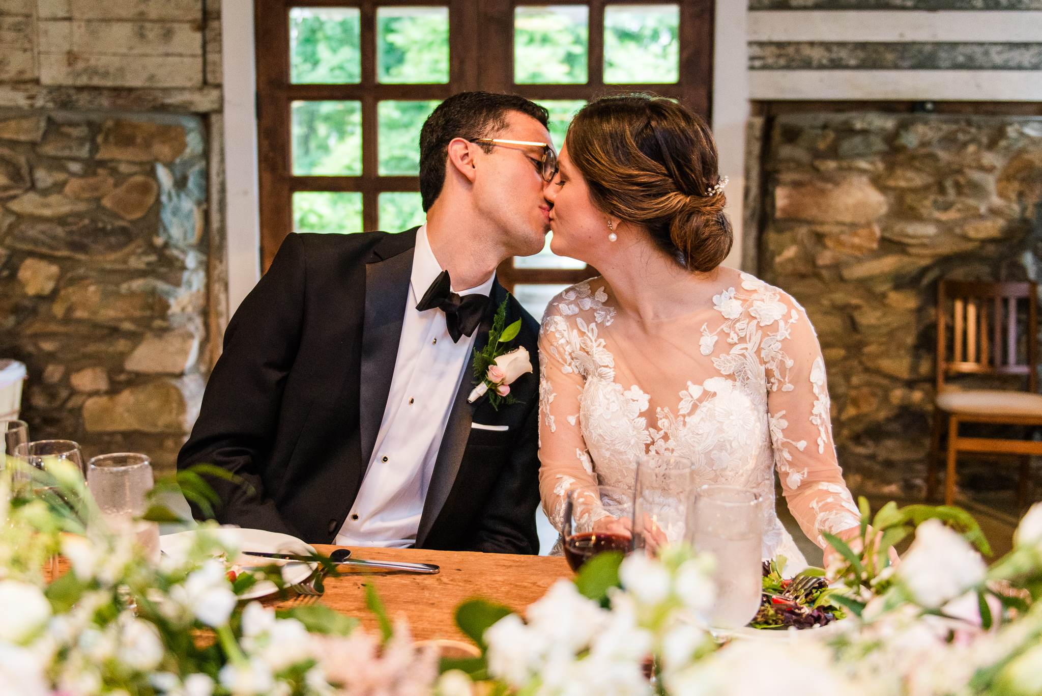 A bride and groom share a kiss at the sweetheart table during their wedding reception at The Barns at Hamilton Station Vineyards in Leesburg, Northern Virginia