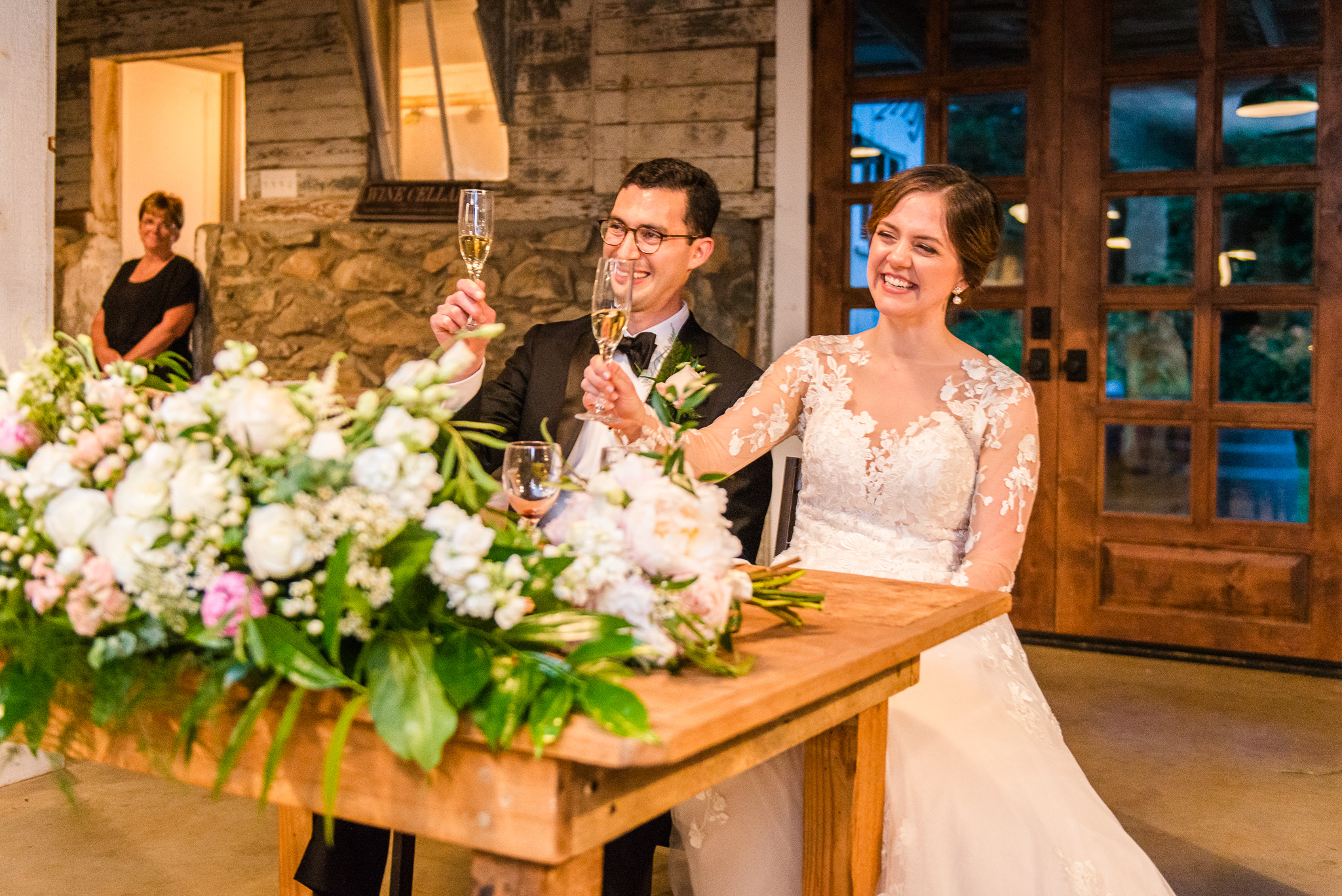 A bride and groom laugh as they raise their champagne glasses for the toasts during their wedding reception at The Barns at Hamilton Station Vineyards in Leesburg, Northern Virginia