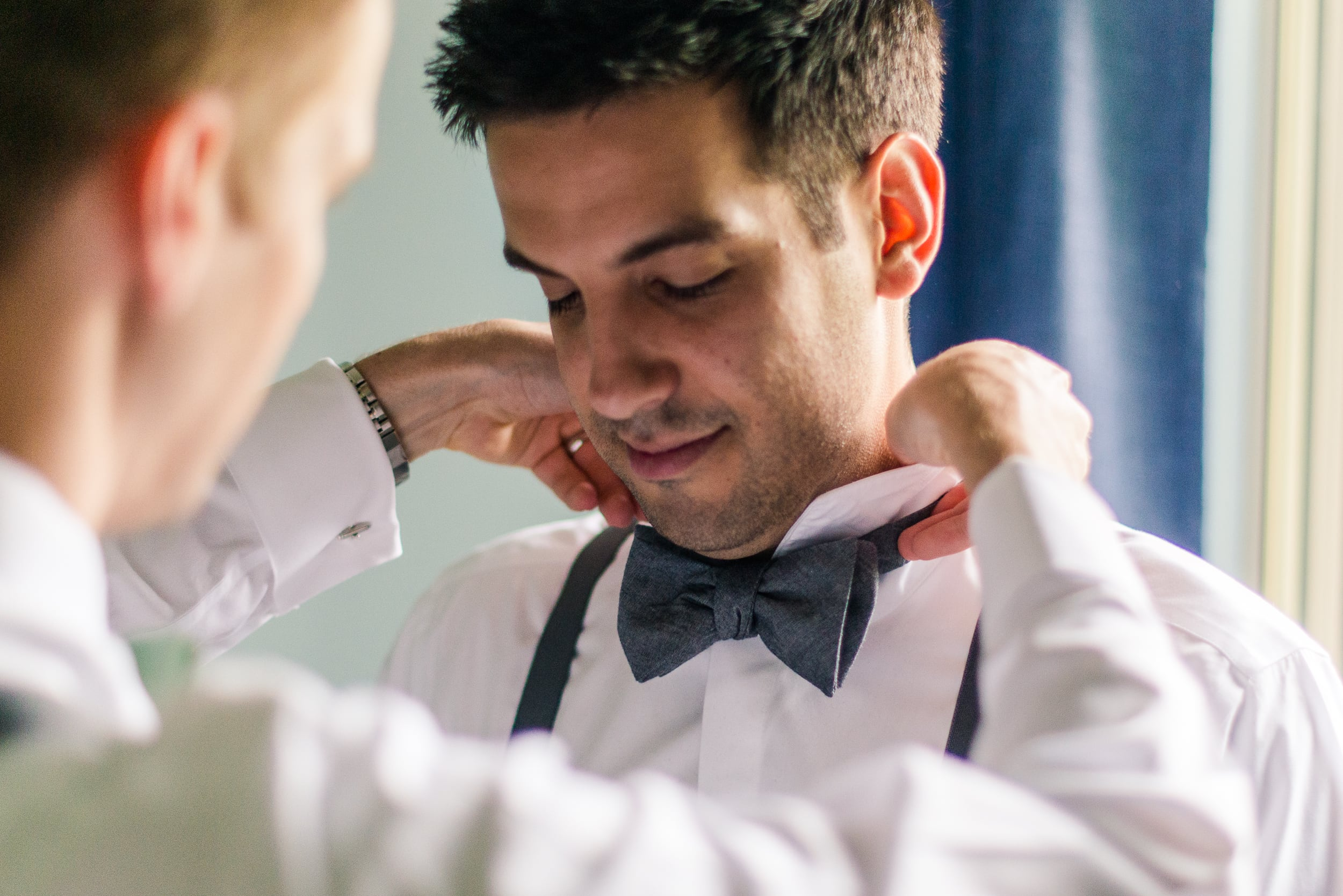 the best man helps the groom get ready for the wedding by putting on his gray bowtie by a window