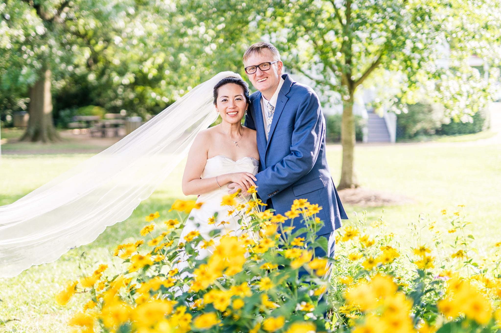 A Taiwanese bride poses with her groom behind wildflowers across from the Vienna Presbyterian Church where they were married in Vienna, Northern Virginia
