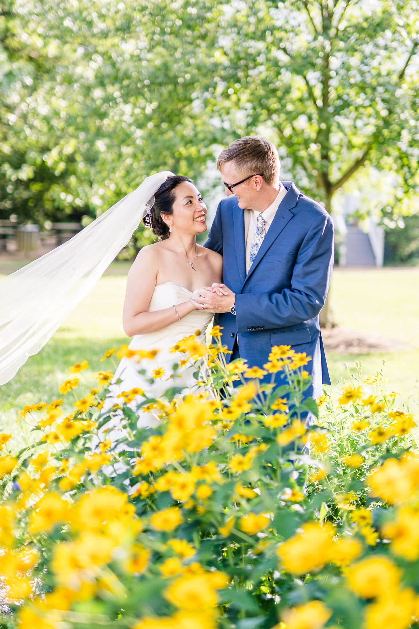A Taiwanese bride looks lovingly at her groom behind wildflowers across from the Vienna Presbyterian Church where they were married in Vienna, Northern Virginia