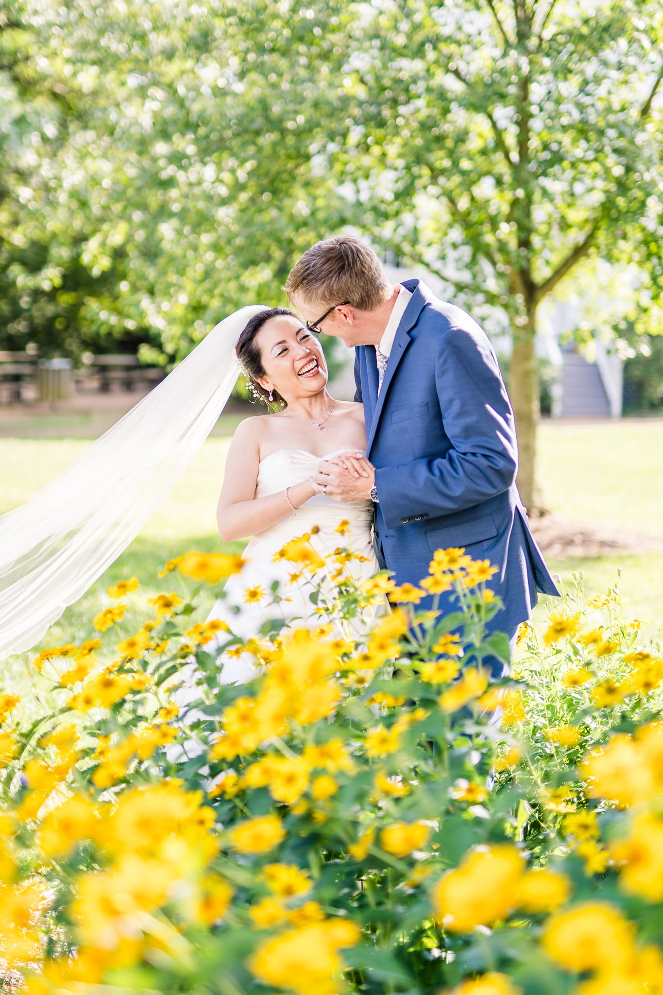 A Taiwanese bride laughs with her groom behind wildflowers across from the Vienna Presbyterian Church where they were married in Vienna, Northern Virginia