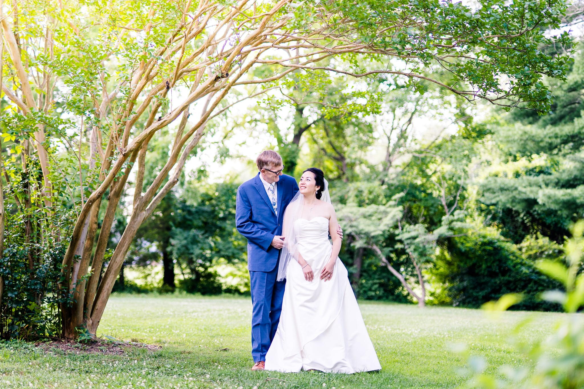 A Taiwanese bride poses with her groom among the greenery at Hunter House at Nottoway Park after their wedding in Vienna, Northern Virginia