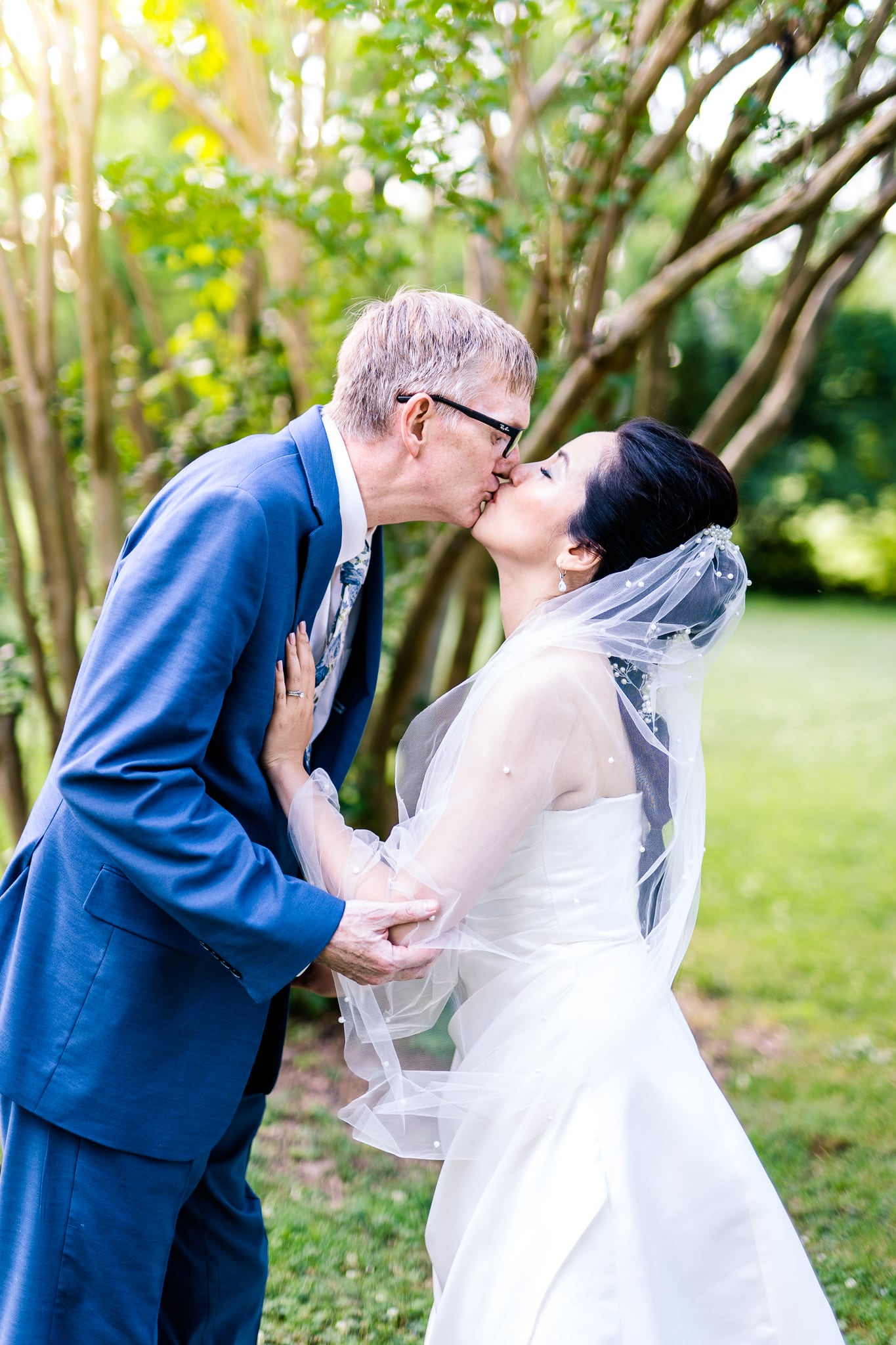 A Taiwanese bride kisses her groom among the greenery at Hunter House at Nottoway Park after their wedding in Vienna, Northern Virginia