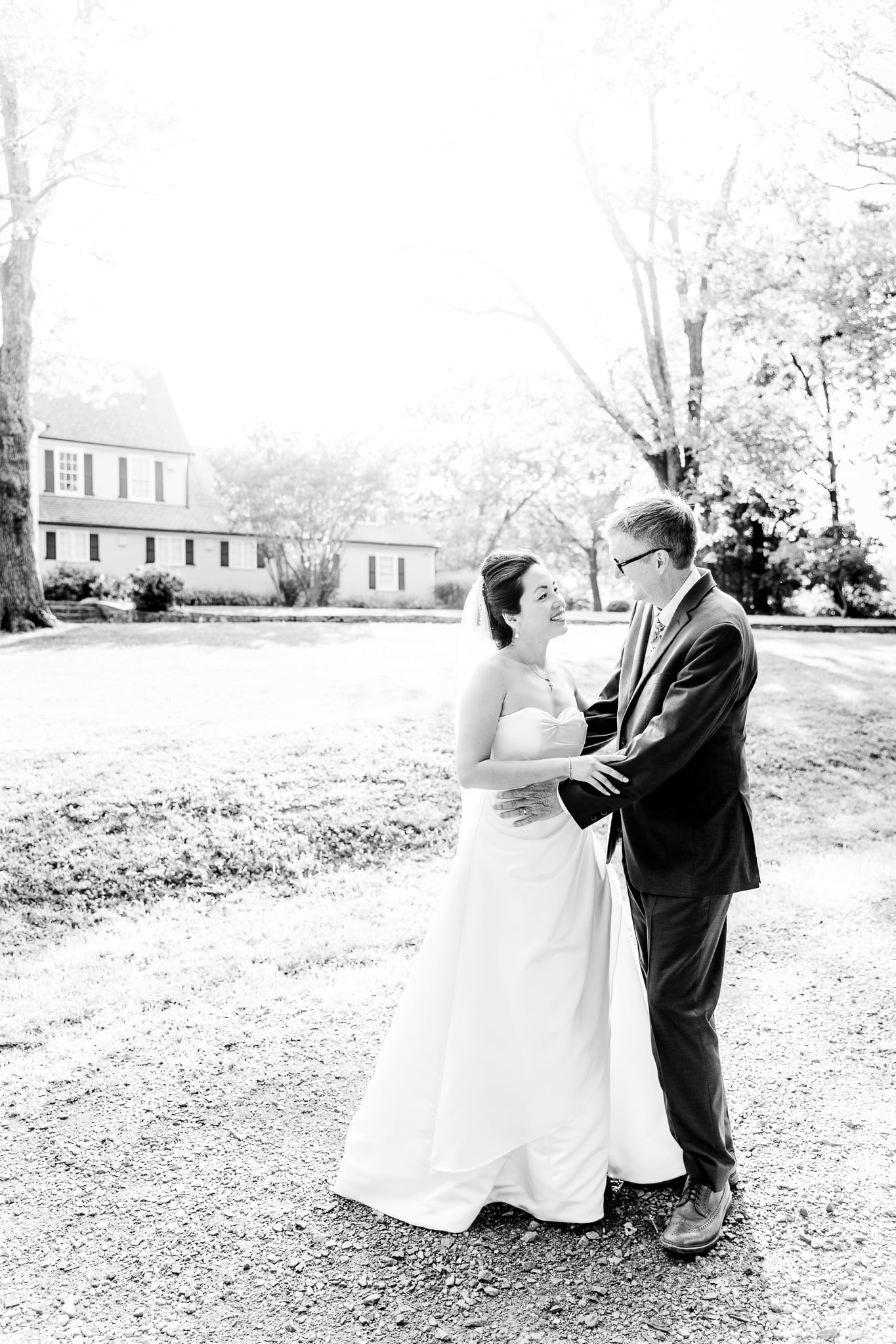 A Taiwanese bride poses with her groom in front of the Hunter House at Nottoway Park after their wedding in Vienna, Northern Virginia