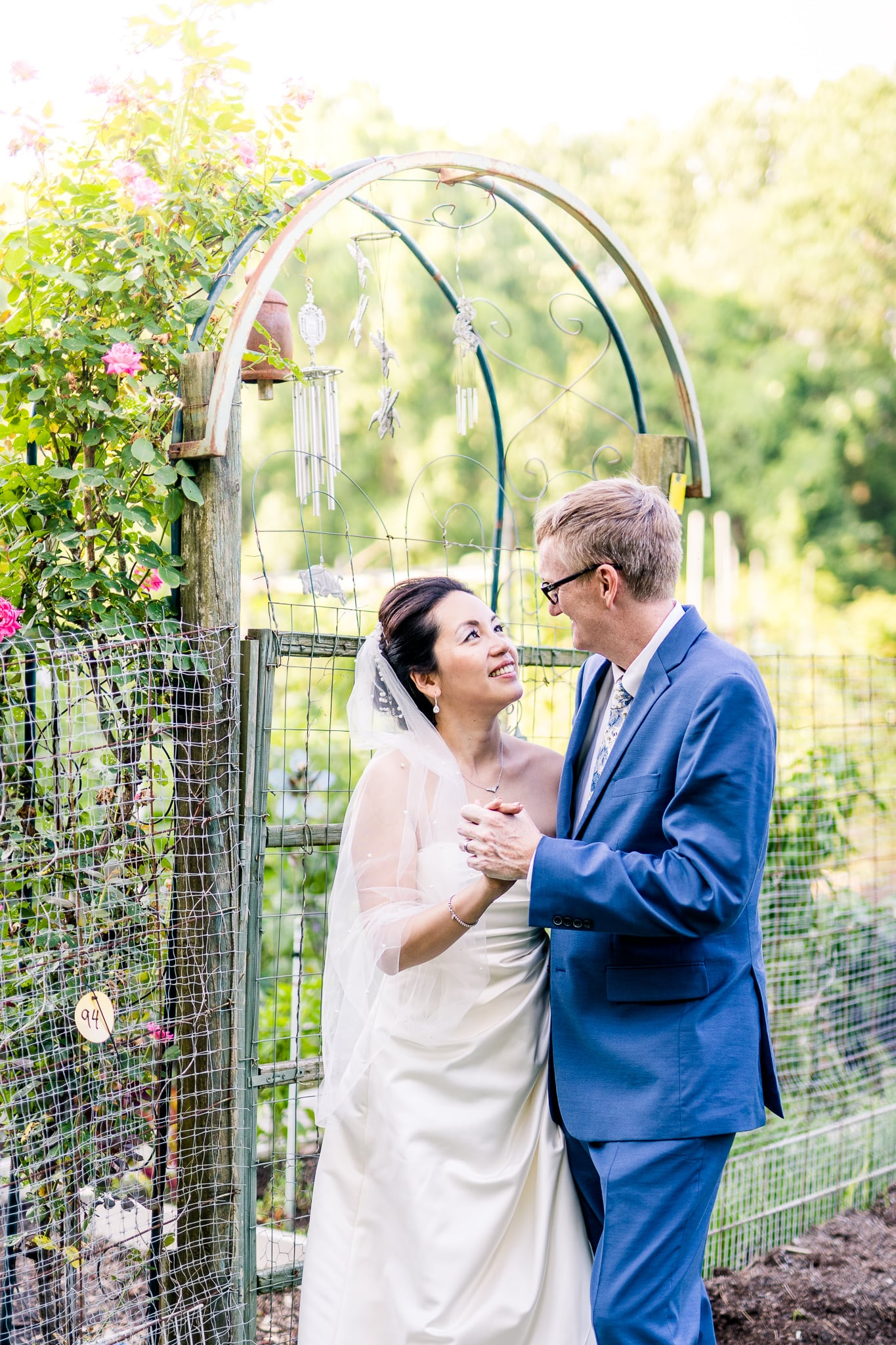 A Taiwanese bride looks at her groom in the community gardens at Nottoway Park after their wedding in Vienna, Northern Virginia