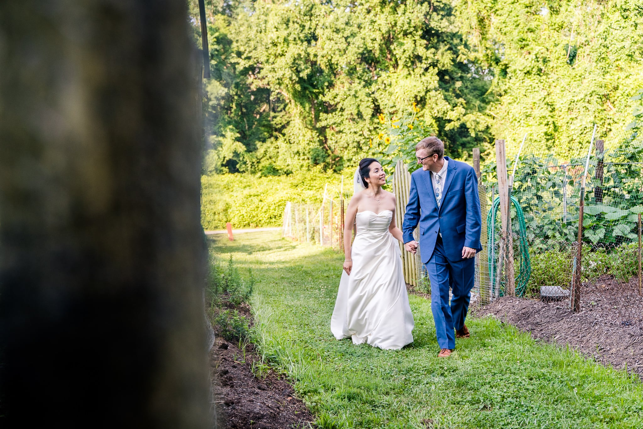 A Taiwanese bride walks with her groom in the community gardens at Nottoway Park after their wedding in Vienna, Northern Virginia