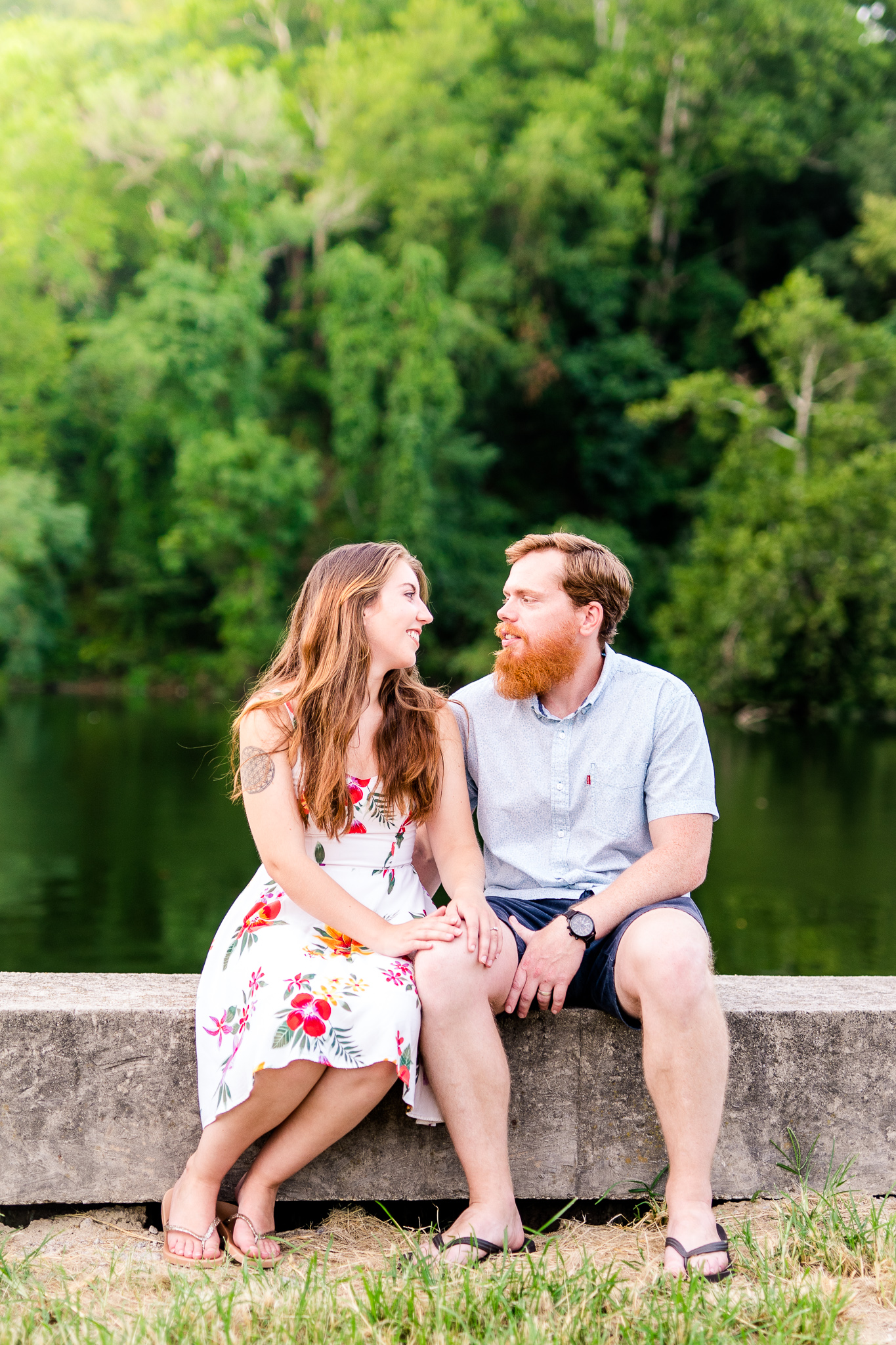 An engaged couple sits together by the water during their summer sunset engagement session in Historic Occoquan, Northern Virginia