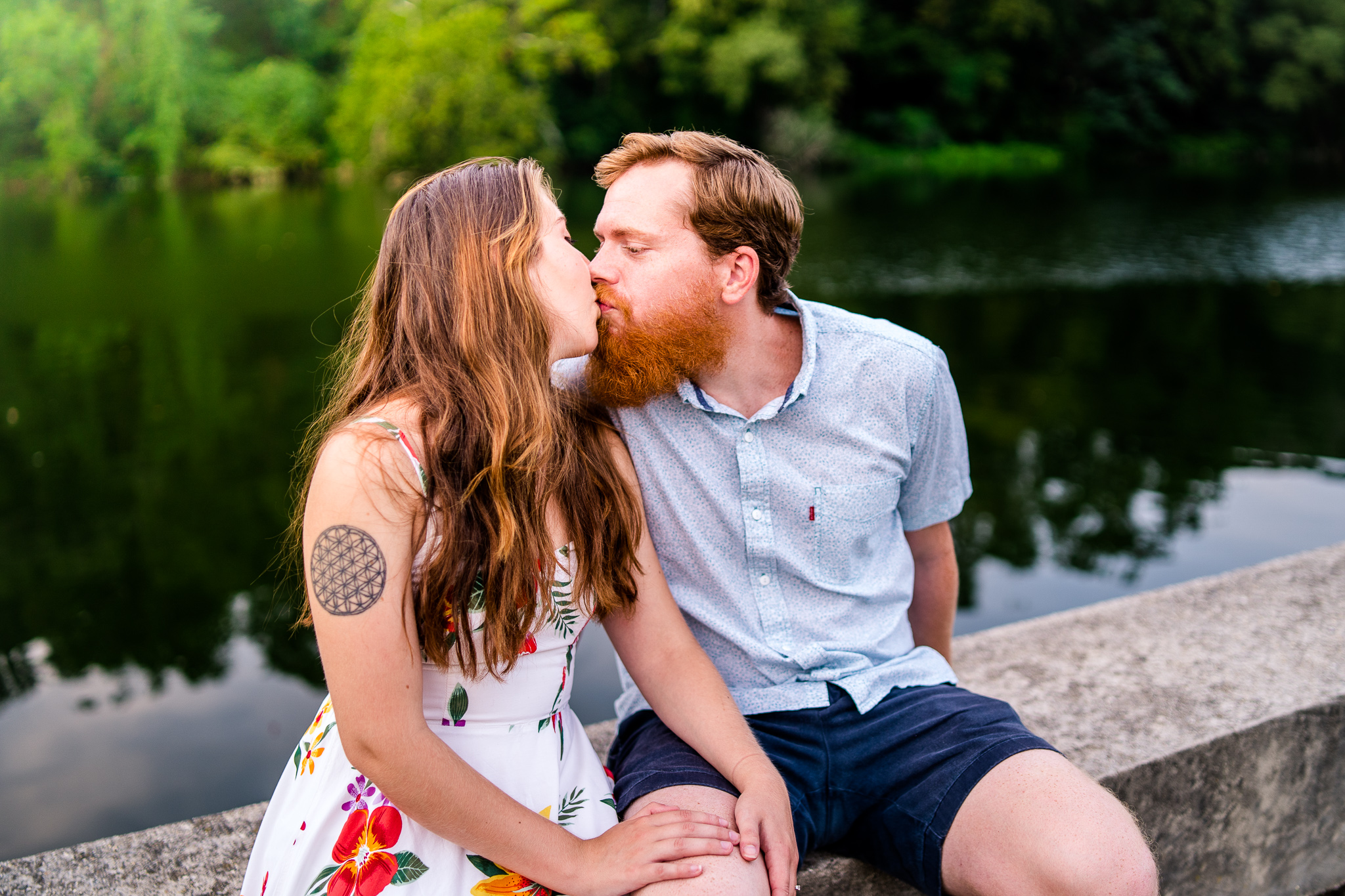 An engaged couple shares a kiss by the water during their summer sunset engagement session in Historic Occoquan, Northern Virginia