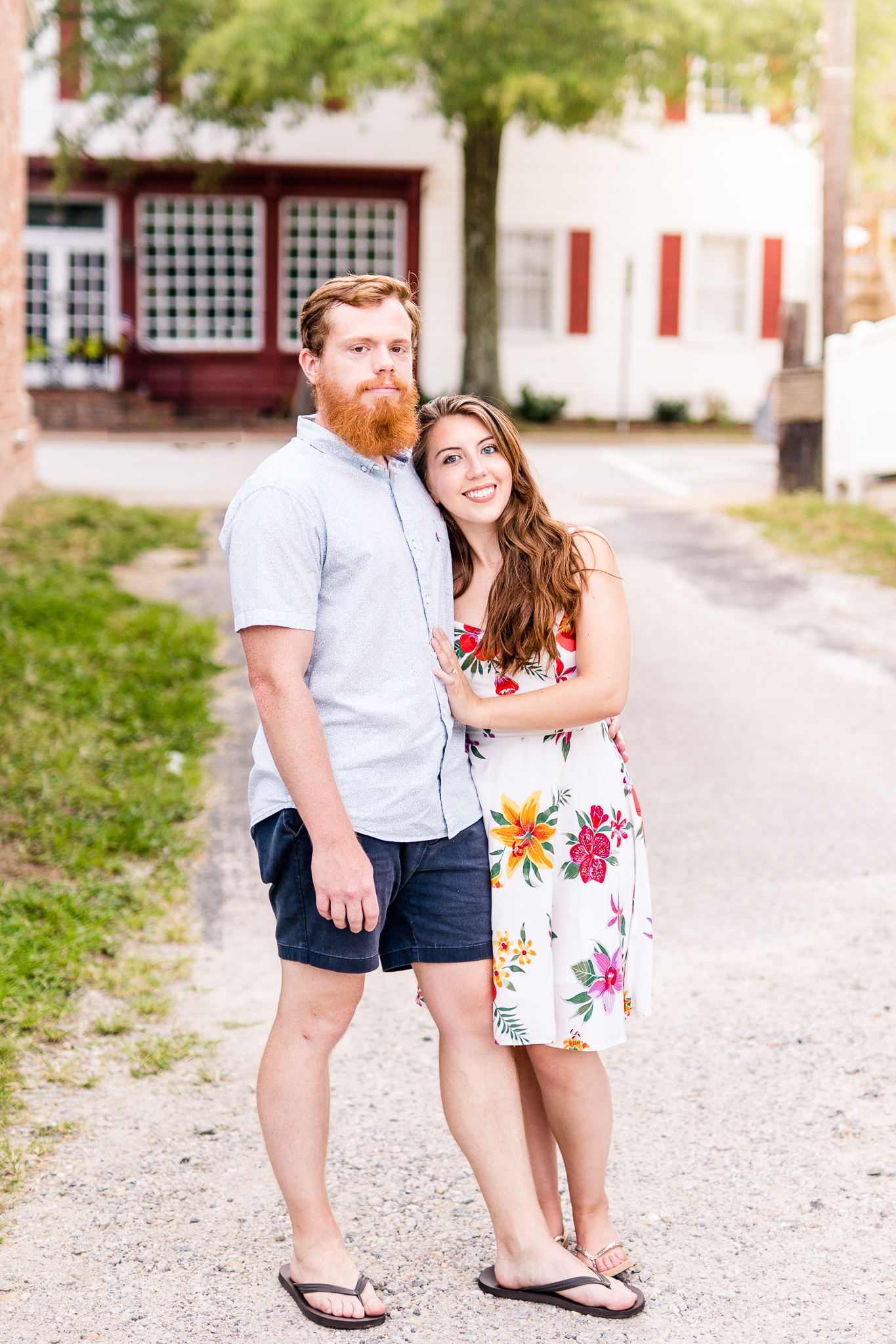 An engaged couple pose together during their summer sunset engagement session in Historic Occoquan, Northern Virginia