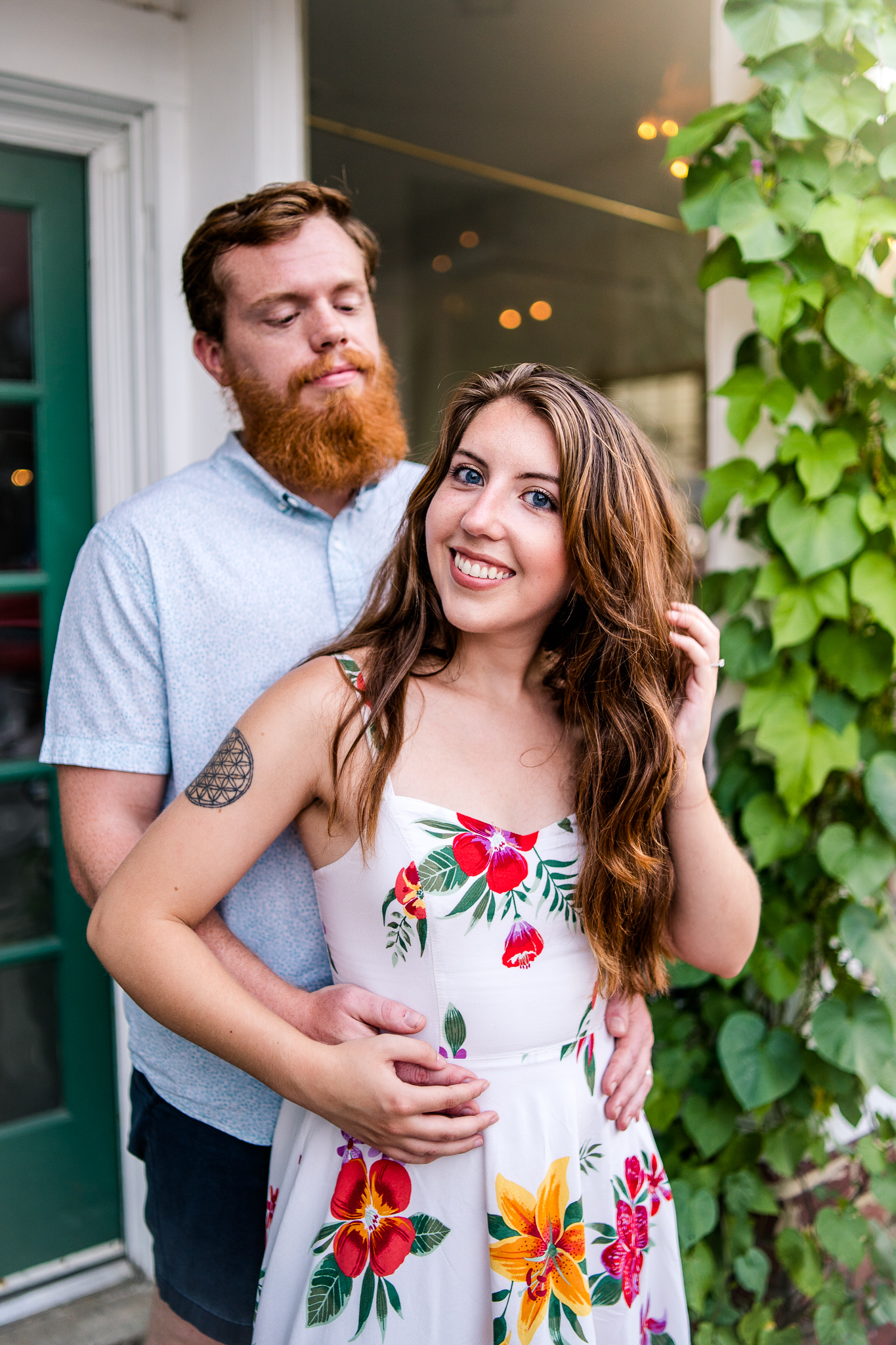 An engaged couple pose in front of a flower shop during their summer sunset engagement session in Historic Occoquan, Northern Virginia