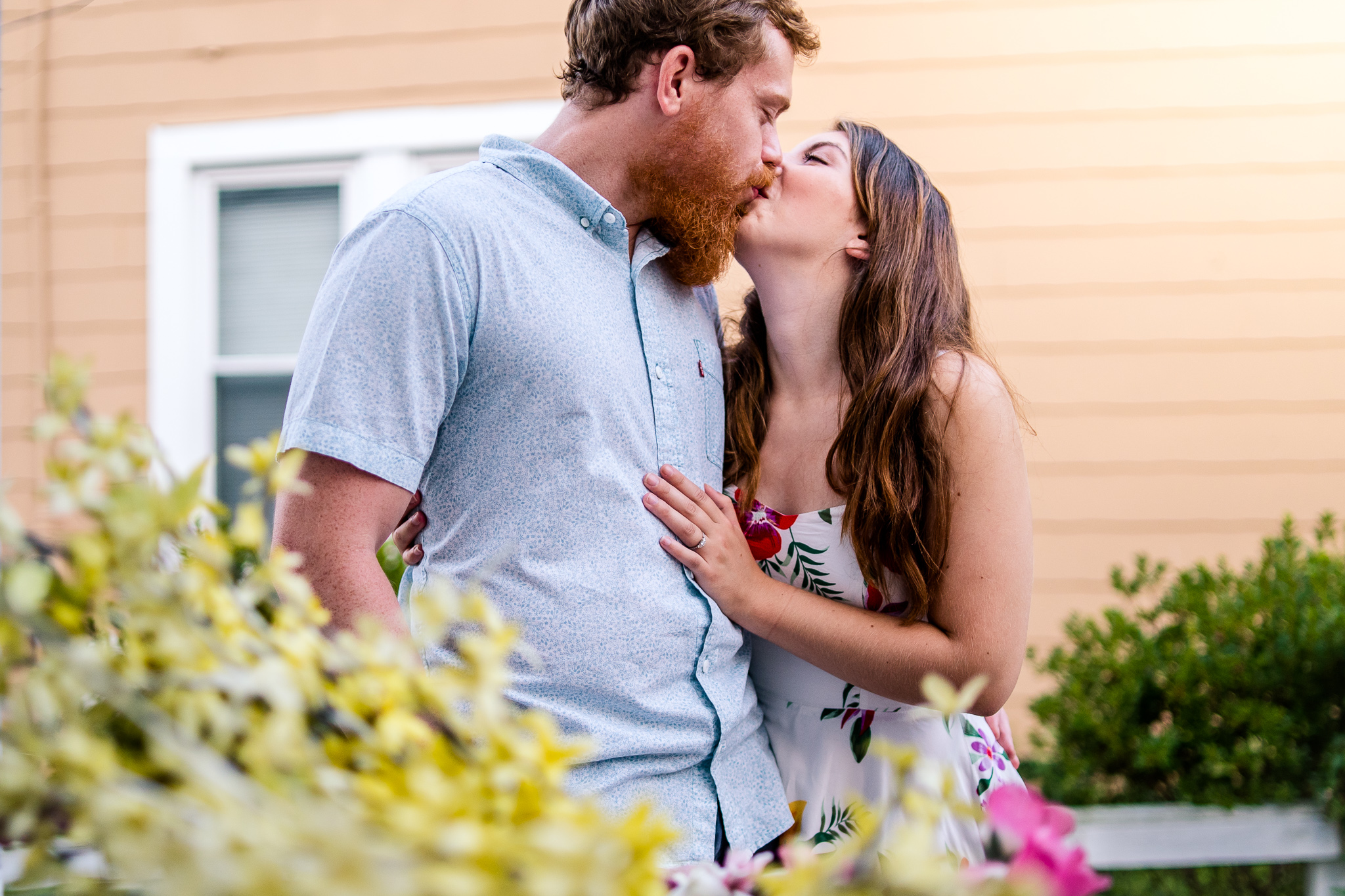 An engaged couple shares a kiss during their summer sunset engagement session in Historic Occoquan, Northern Virginia