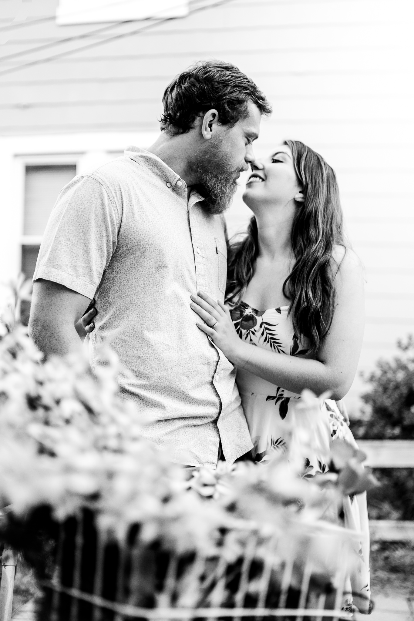 An engaged couple leans in for a kiss during their summer sunset engagement session in Historic Occoquan, Northern Virginia