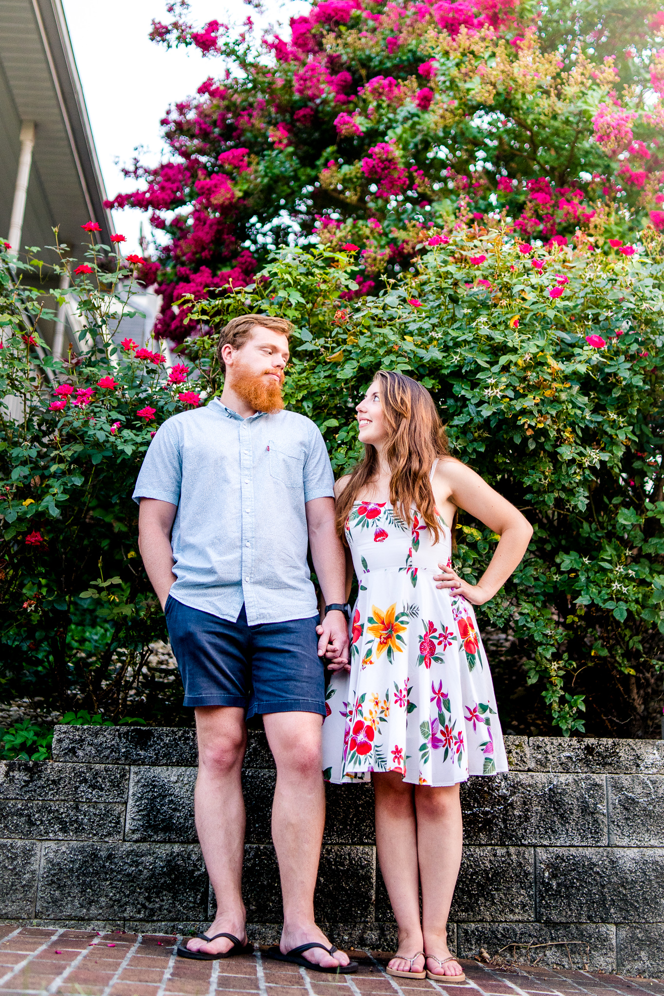 An engaged couple stands together in front of a flower garden during their summer sunset engagement session in Historic Occoquan, Northern Virginia