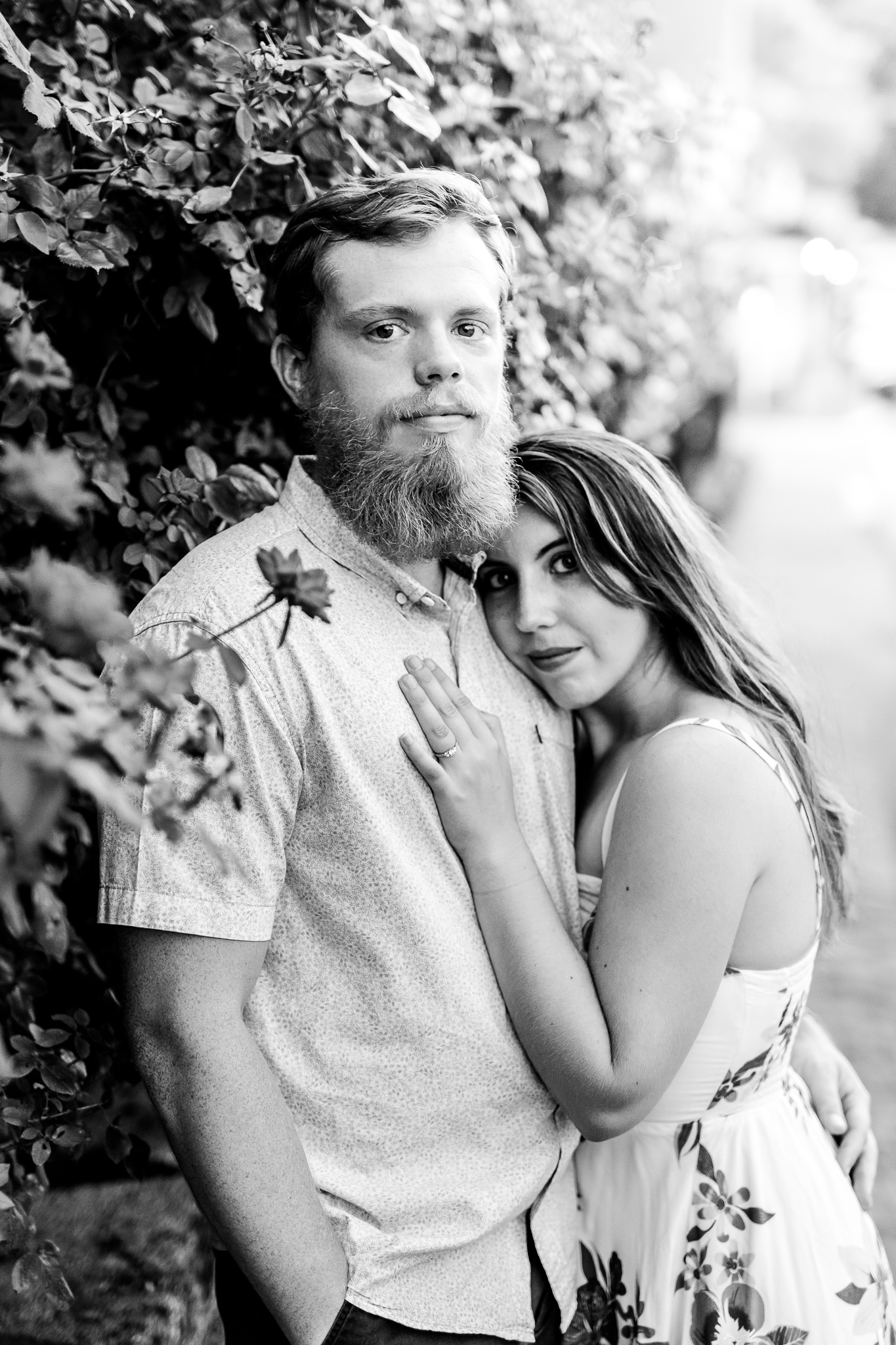 An engaged couple stand together with her head on his shoulder near a garden during their summer sunset engagement session in Historic Occoquan, Northern Virginia