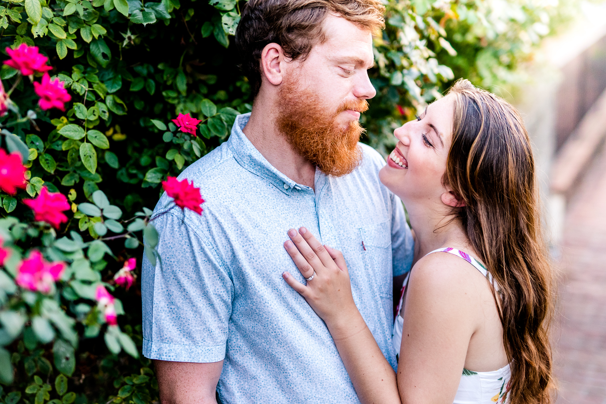 An engaged couple look lovingly at each other next to a rose bush during their summer sunset engagement session in Historic Occoquan, Northern Virginia