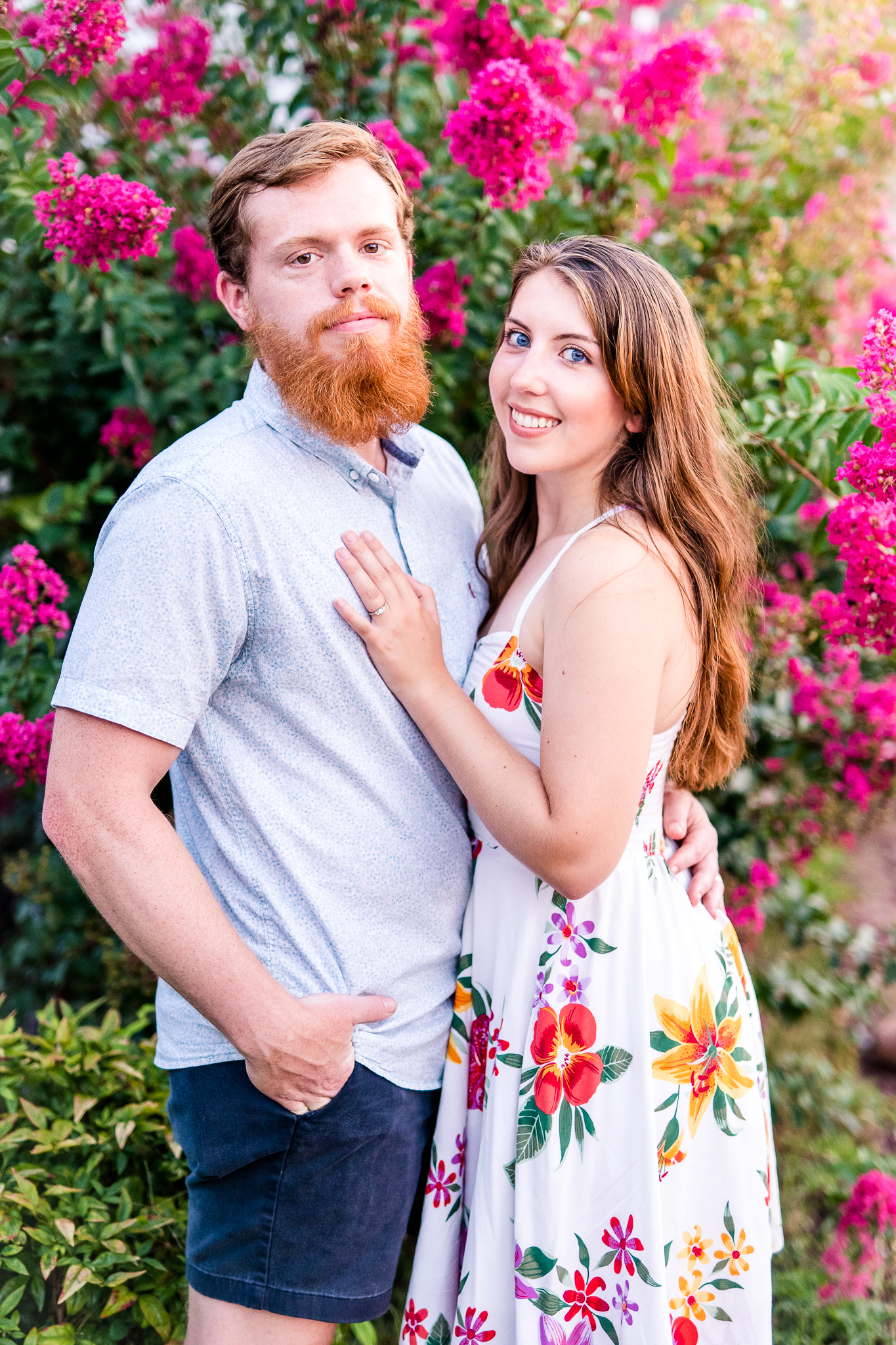 An engaged couple poses next to a flowering tree during their summer sunset engagement session in Historic Occoquan, Northern Virginia