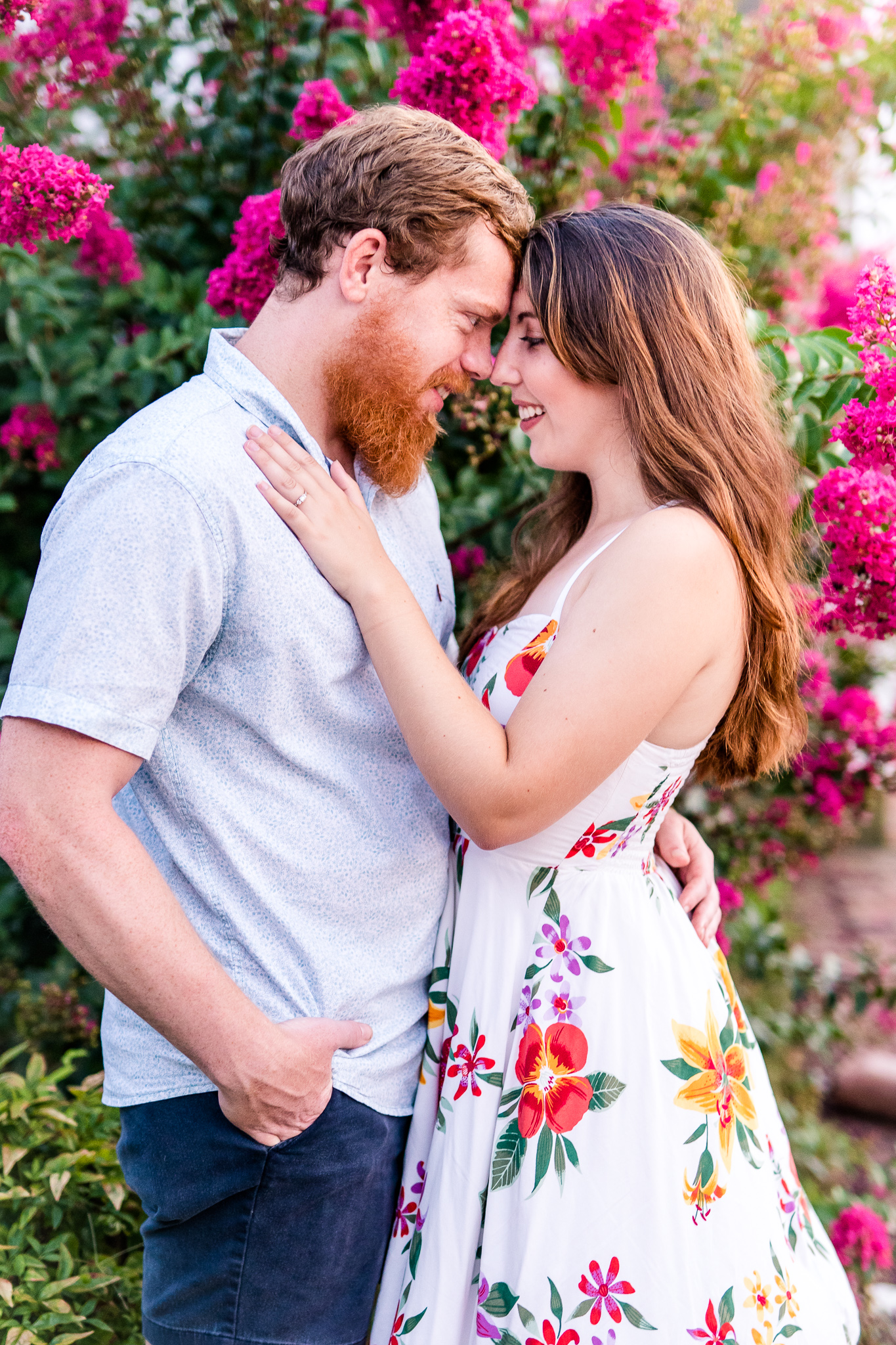 An engaged couple smile with their foreheads pressed together in front of a pink flowering tree during their summer sunset engagement session in Historic Occoquan, Northern Virginia