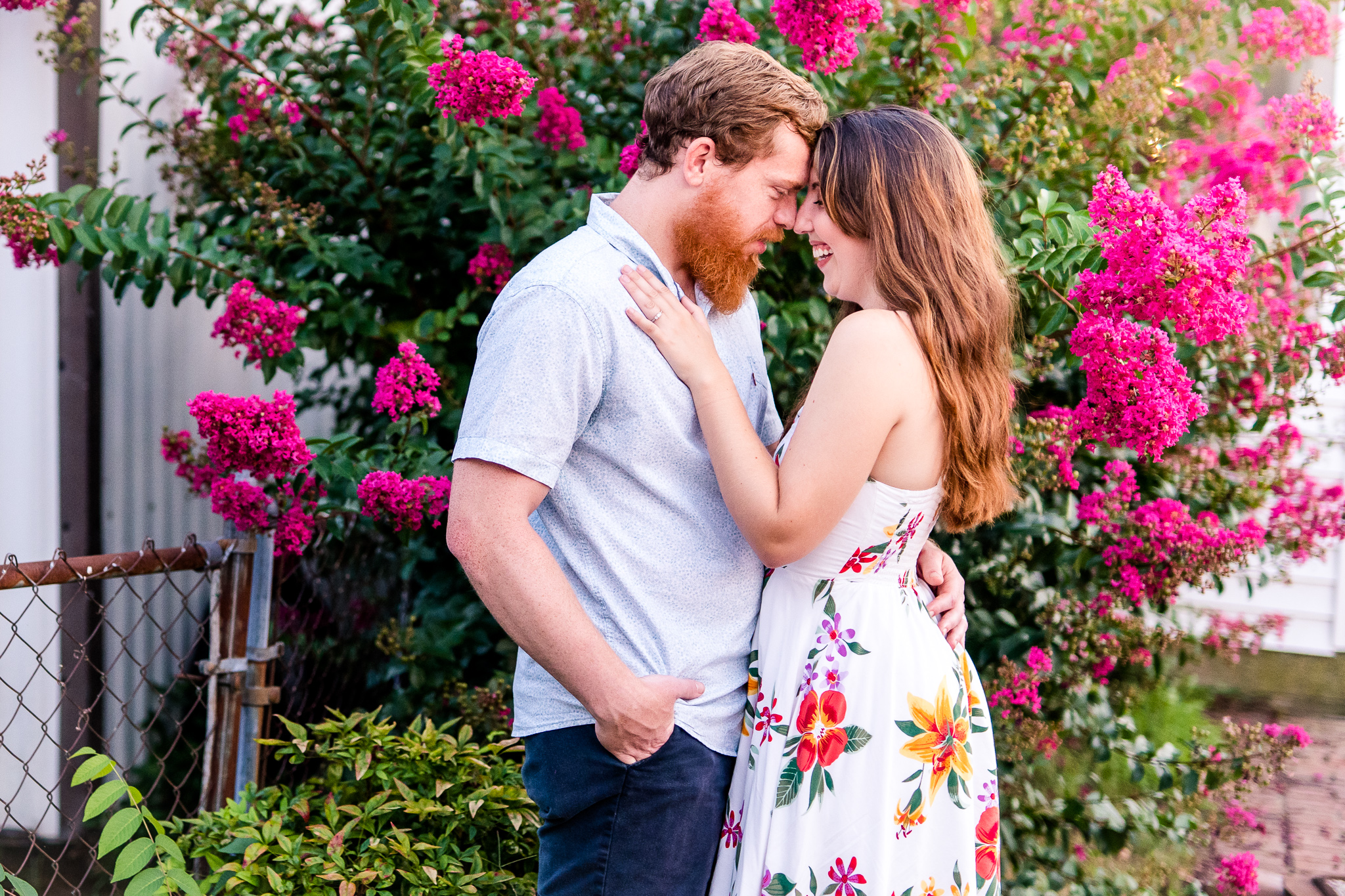 An engaged couple press their foreheads together and laugh during their summer sunset engagement session in Historic Occoquan, Northern Virginia