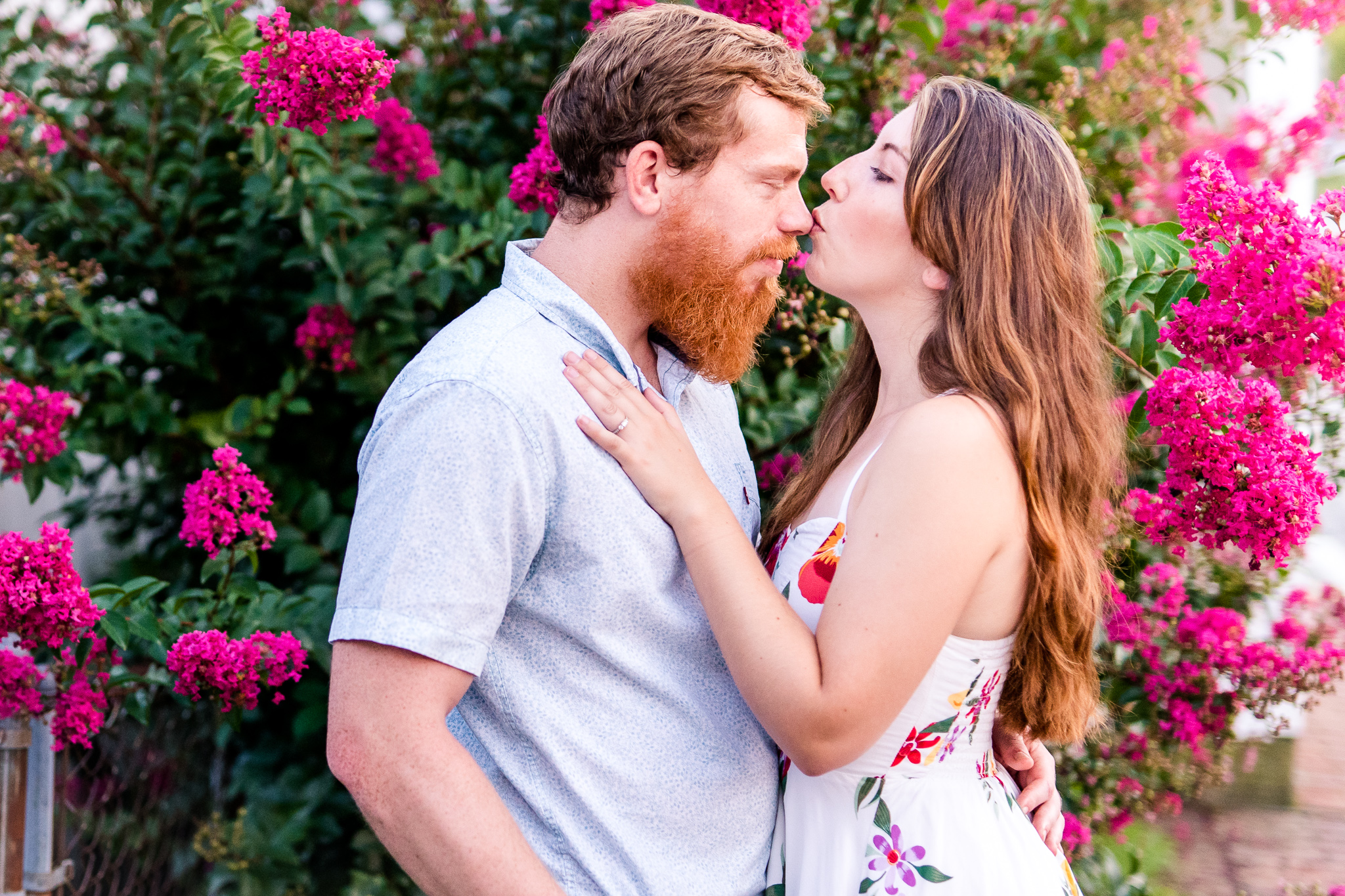 A woman kisses her fiance on the nose as they stand in front of a pink flowering tree during their summer sunset engagement session in Historic Occoquan, Northern Virginia