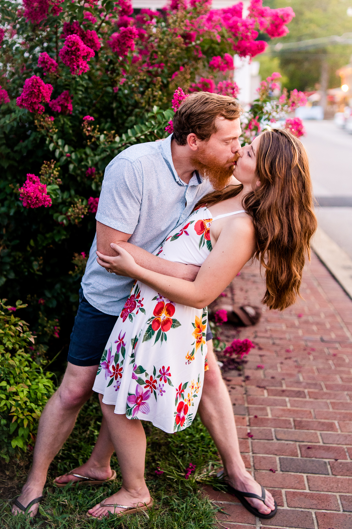 An engaged couple shares a dramatic kiss in front of a pink flowering tree during their summer sunset engagement session in Historic Occoquan, Northern Virginia