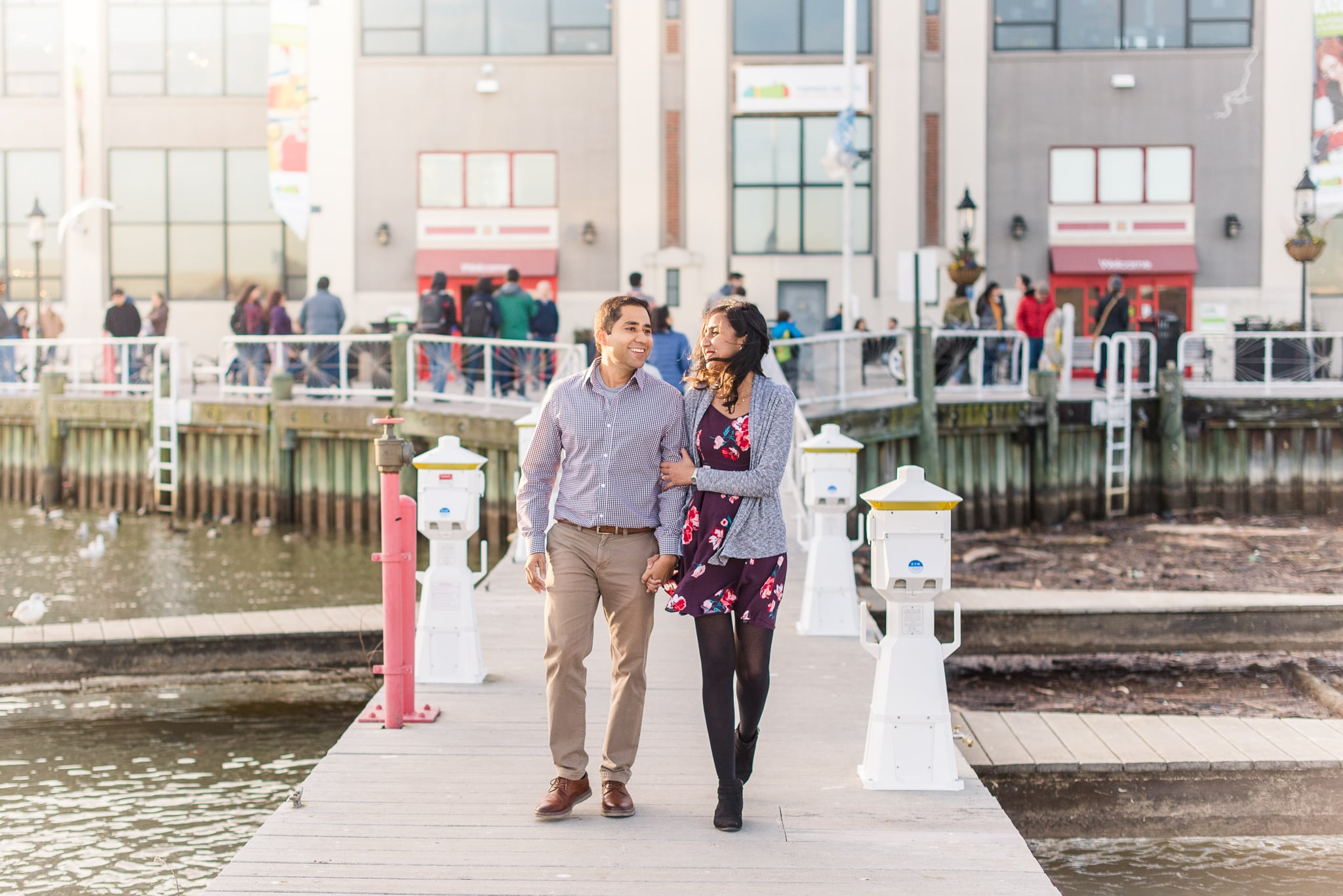 An engaged couple walks together along the pier at Old Town Alexandria in Northern Virginia