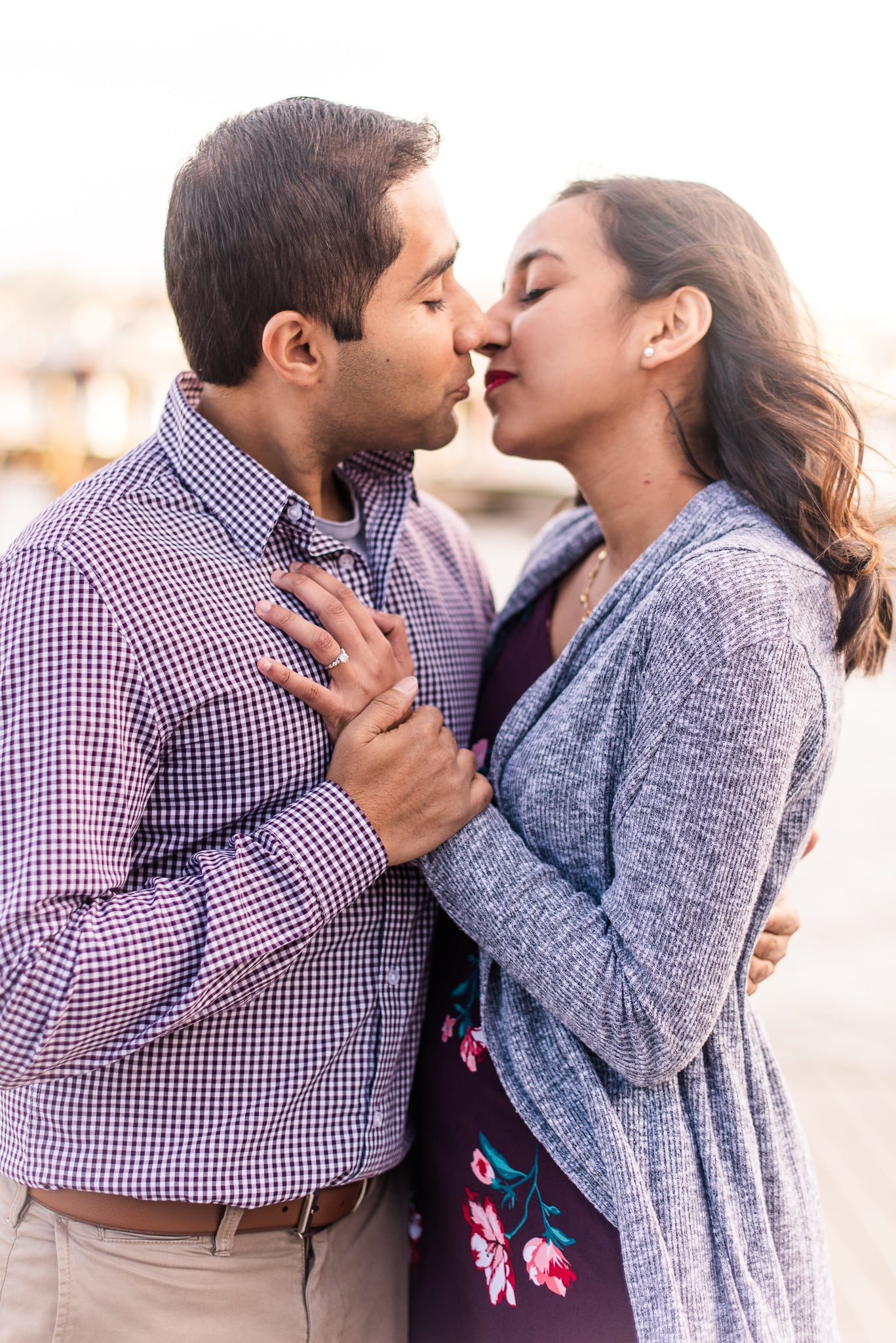 An engaged couple leans in for a kiss as they stand on the docks by the Potomac River during their engagement session in Old Town Alexandria