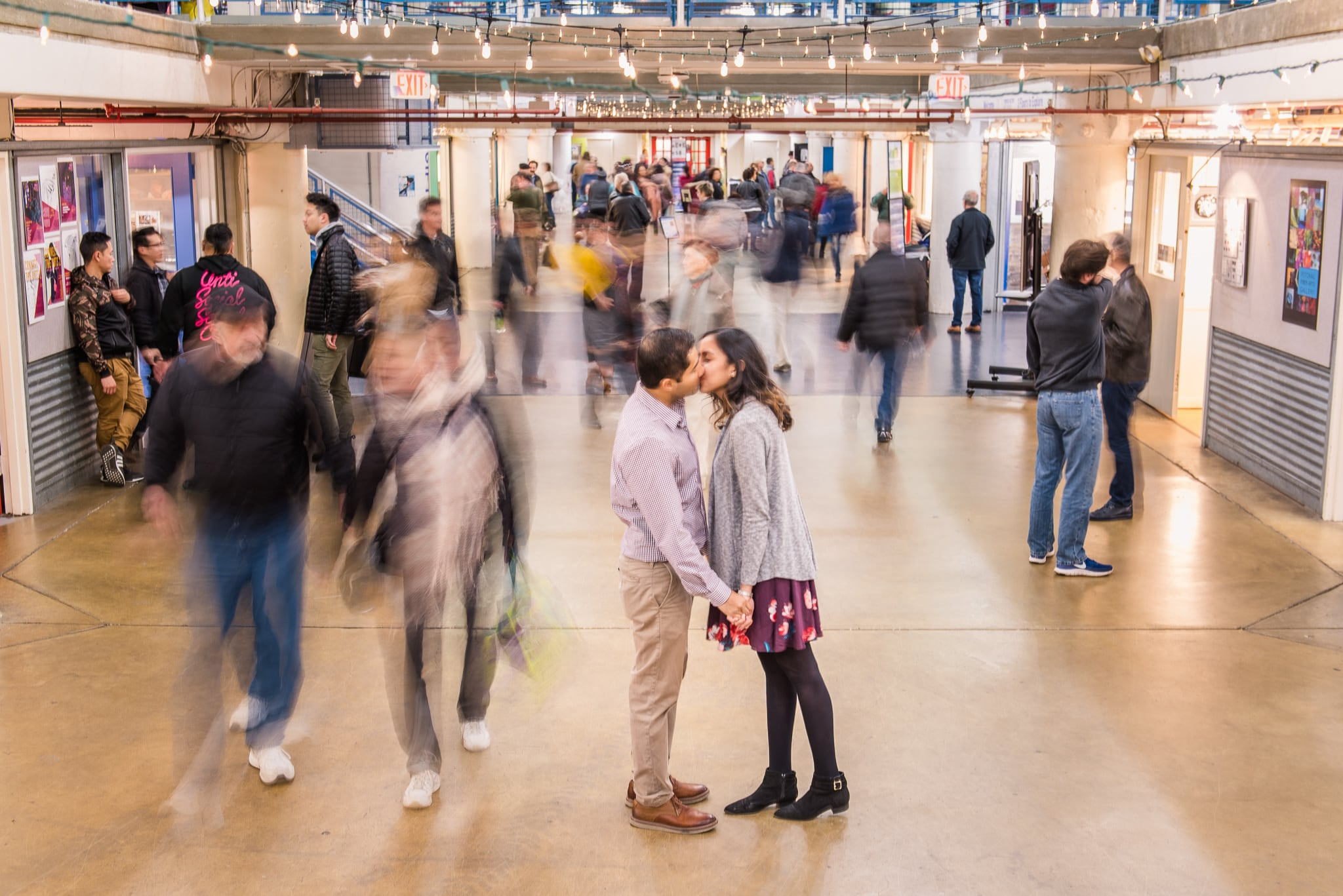 An engaged couple shares a kiss as they stand inside the busy Torpedo Factory Art Center during their engagement session in Old Town Alexandria
