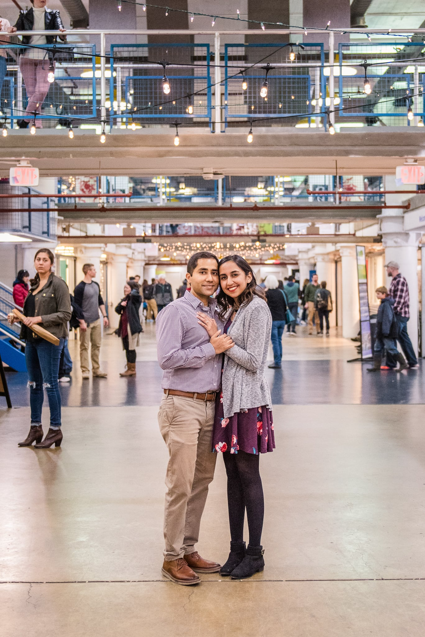 An engaged couple stands together inside the busy Torpedo Factory Art Center during their engagement session in Old Town Alexandria
