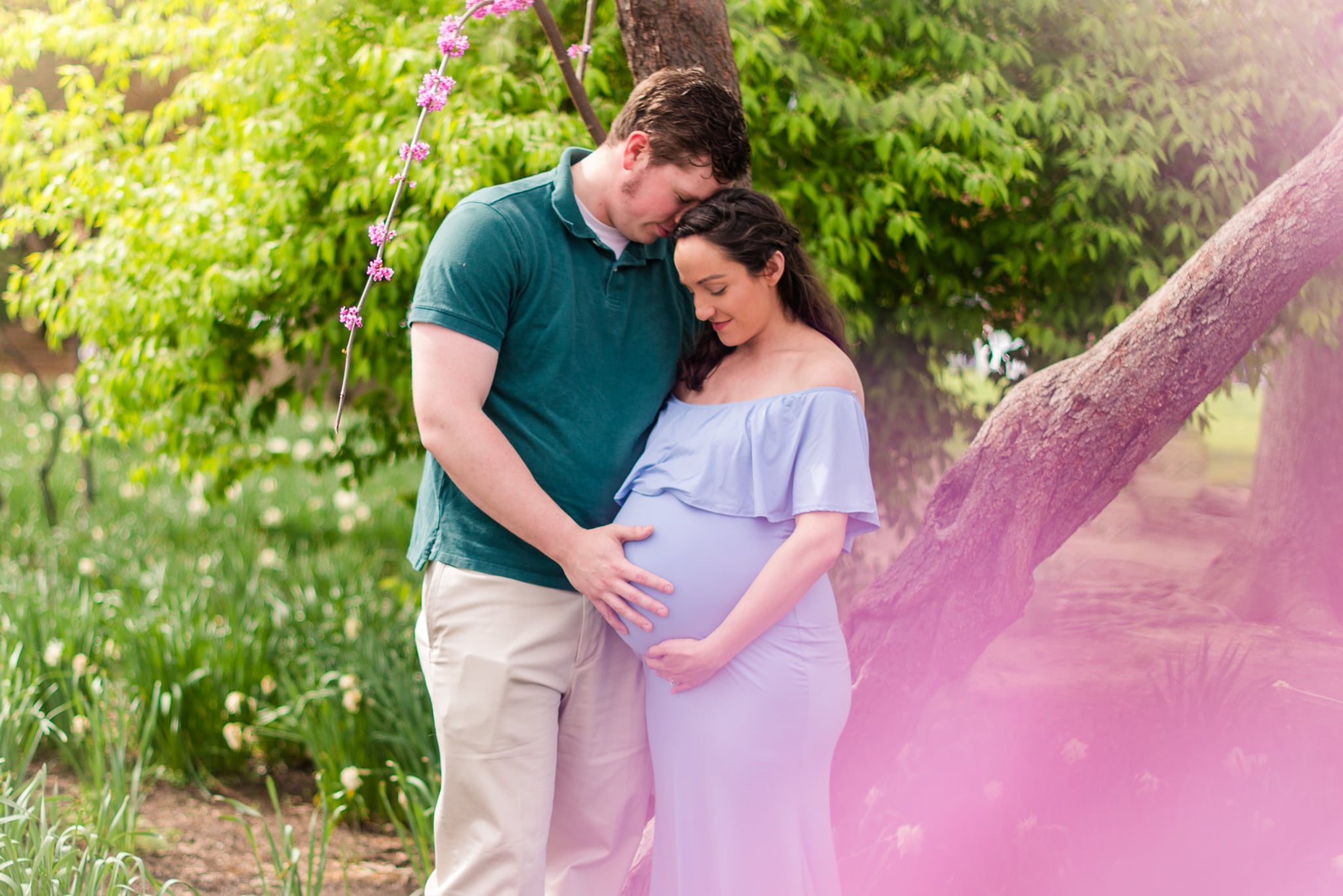 A pregnant woman poses in a blue gown with her husband in Waterfront Park for her spring maternity session in Old Town Alexandria