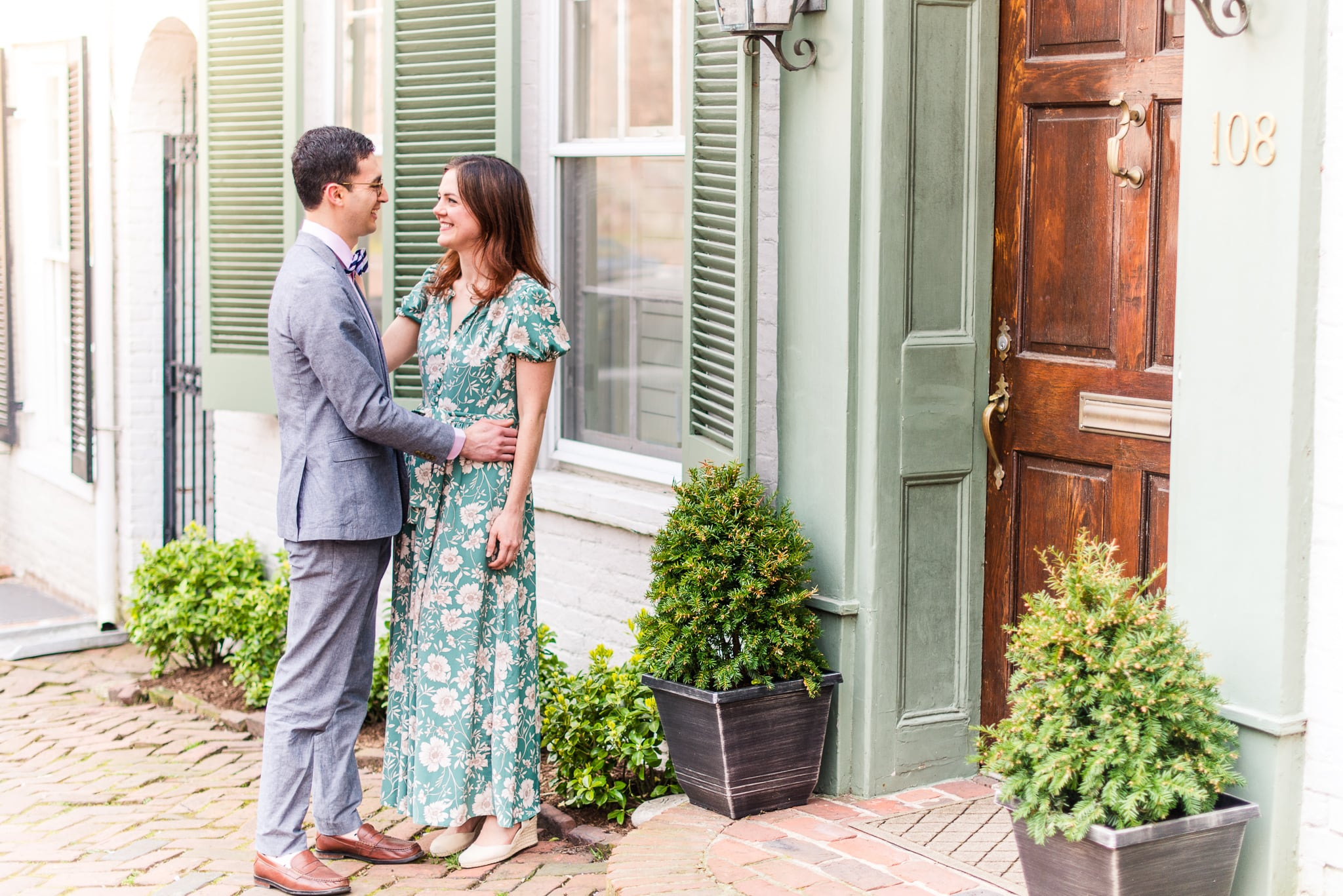 An engaged couple stand together on the sidewalk outside a historic building during their engagement session in Old Town Alexandria