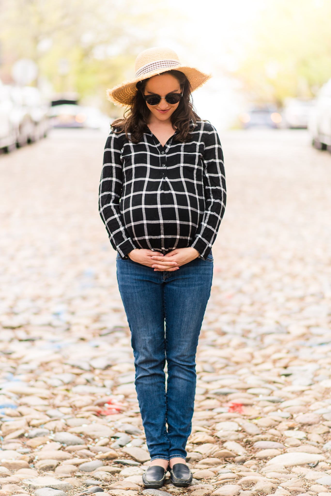 A pregnant woman poses along the cobblestone street during her maternity session in Old Town Alexandria
