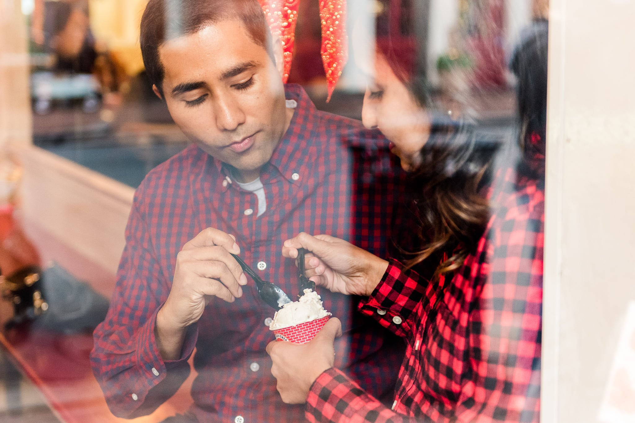 An engaged couple shares ice cream from Pop's Old Fashioned Ice Cream during their engagement session in Old Town Alexandria