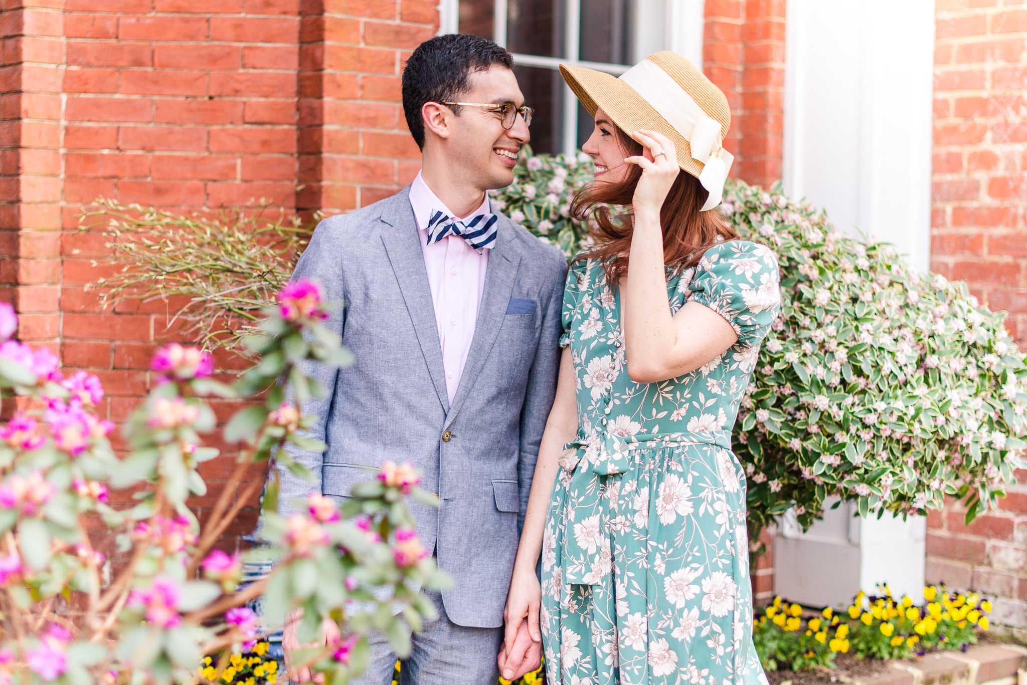 An engaged couple stands together as a breeze blows through the spring flowers around them during their engagement session in Old Town Alexandria