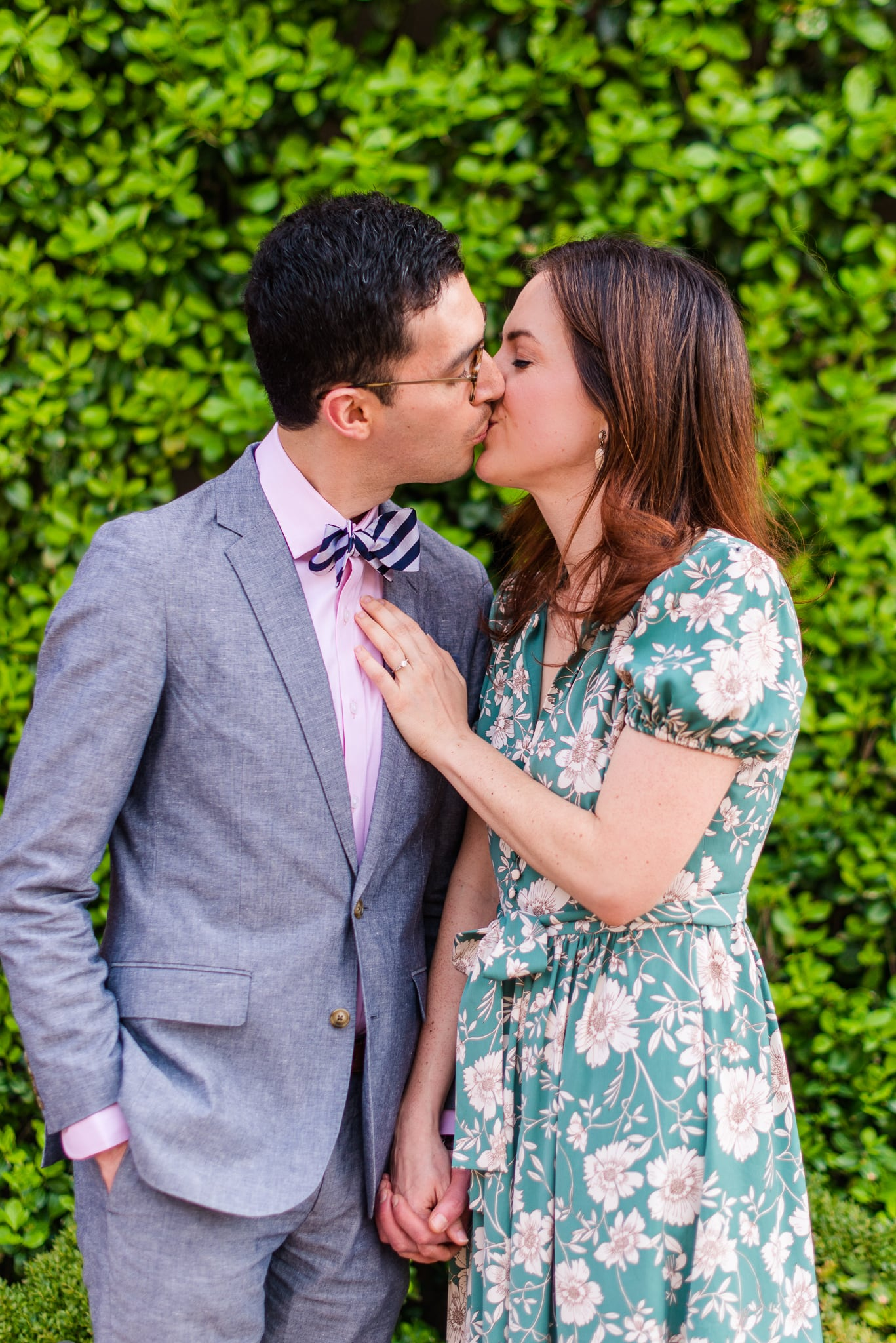 An engaged couple shares a kiss in front of a wall of shrubbery during their engagement session in Old Town Alexandria